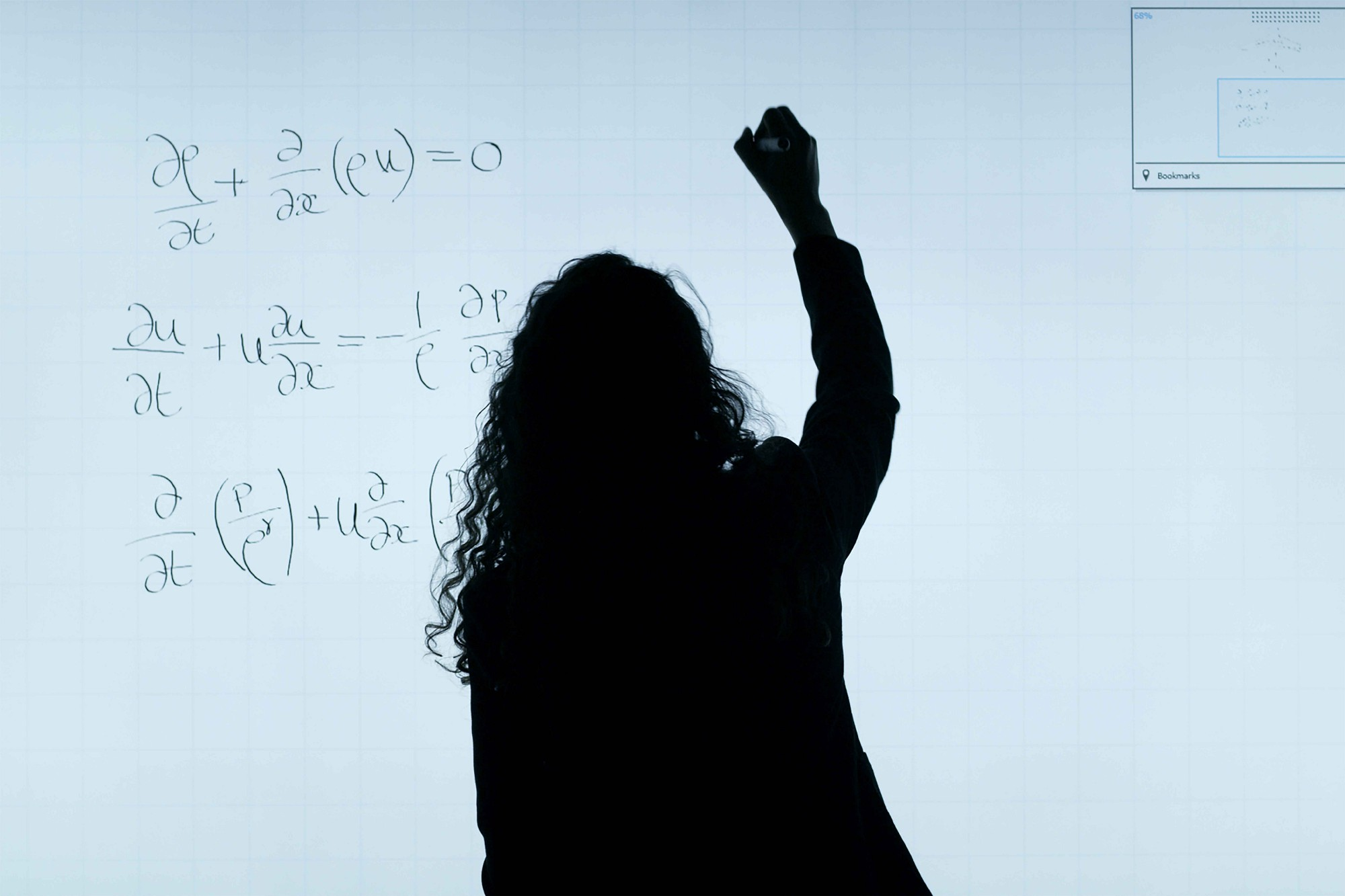 Sillouhette of a woman writing calculus formulas on a white board.