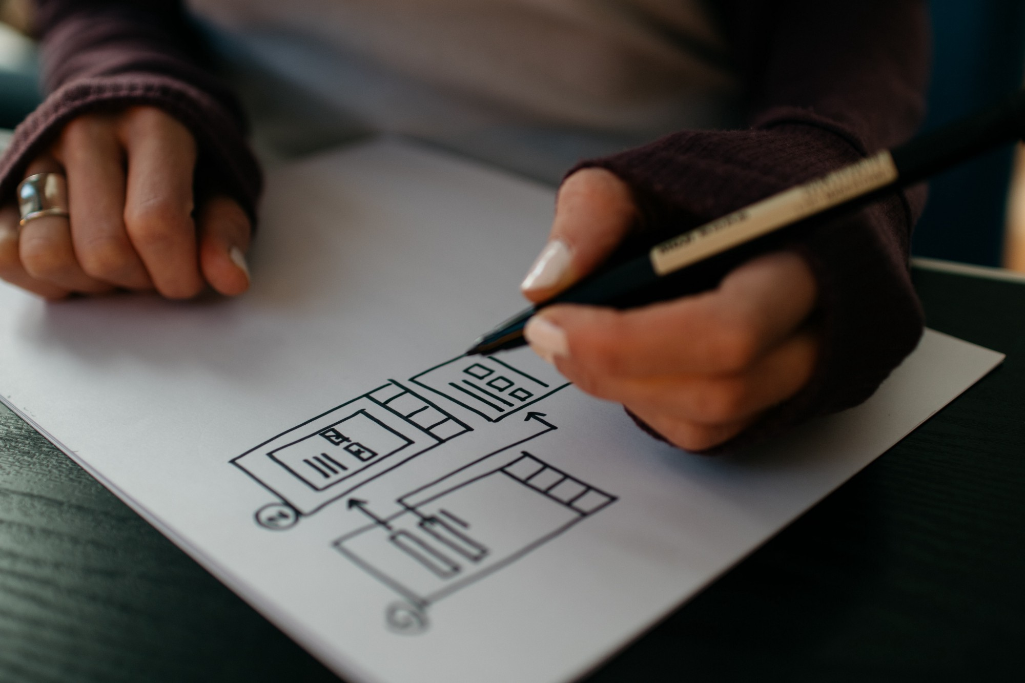 woman drawing wireframe with pen on paper