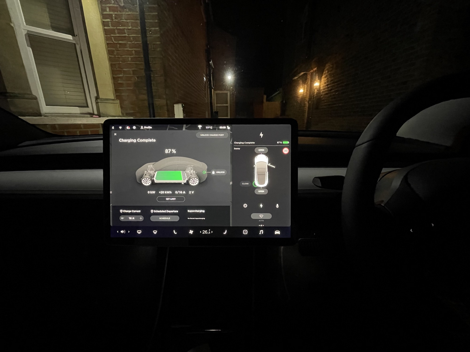 Photo of the Model 3 infotainment system at night with a house behind it