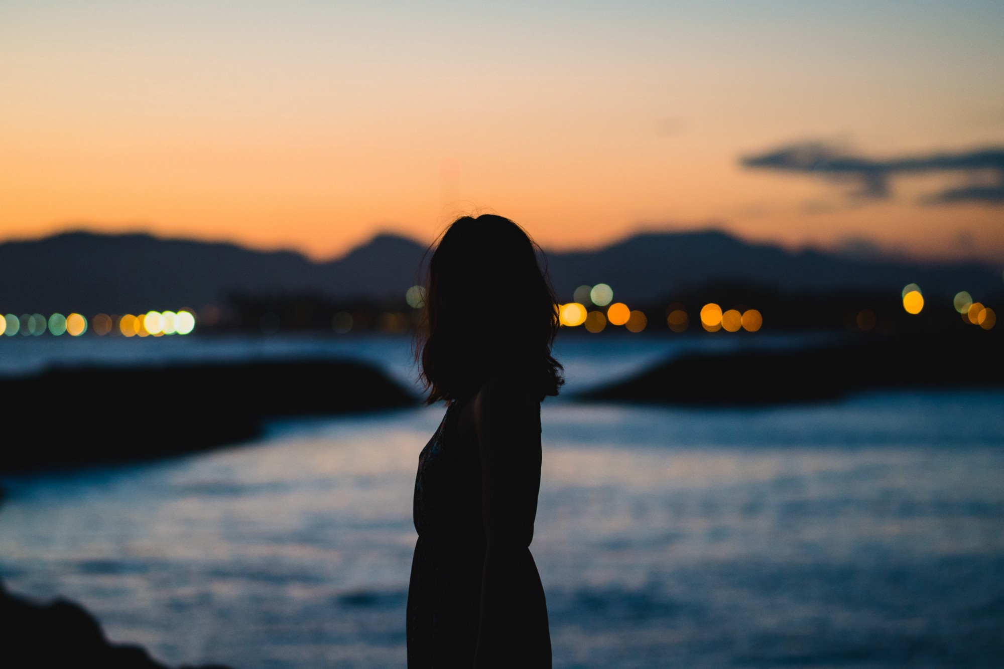 The silhouette of a woman looking out to sea in late evening.
