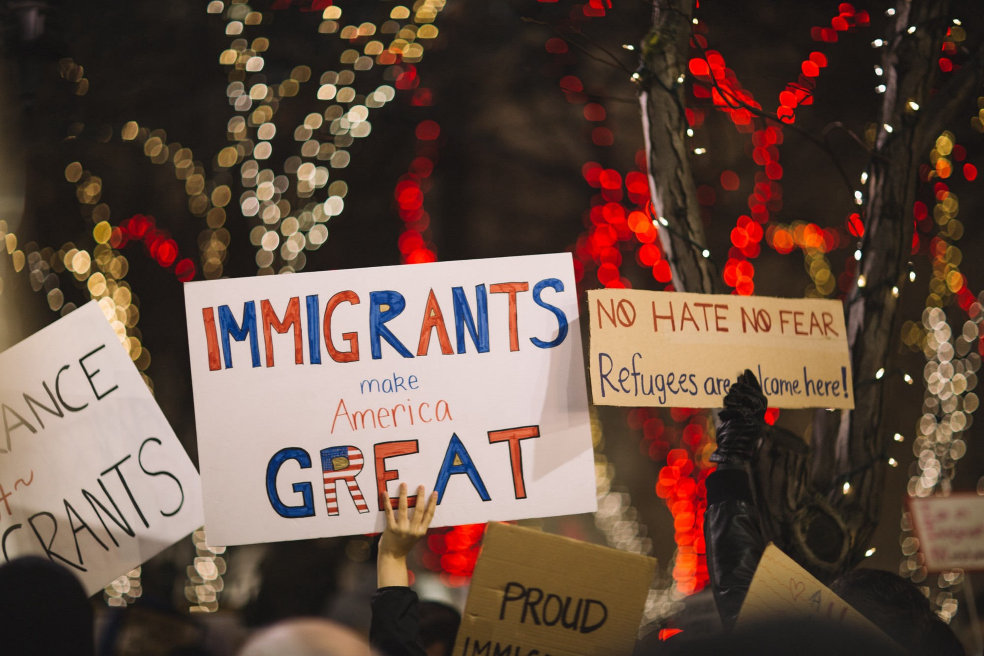 "Immigrants holding signs that said ""Immigrants make America great""."