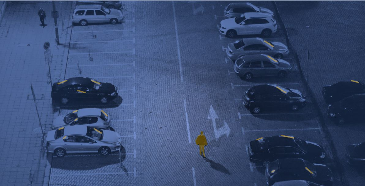A single highlighted figure walks alone through a field of cars at night