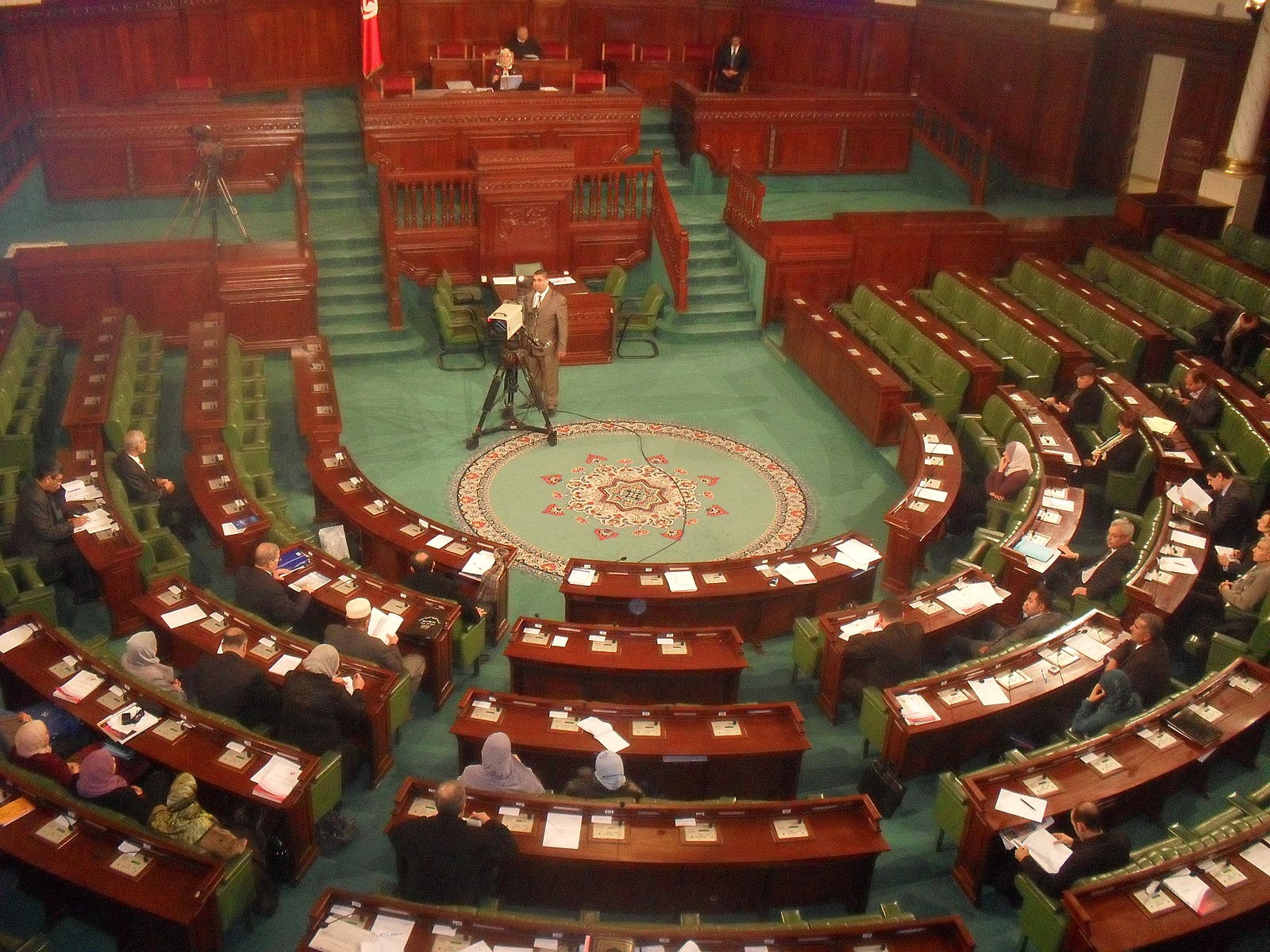 Tunisian Parliament in a horse shoe shape, with parliamentarians and a TV camera looking on.