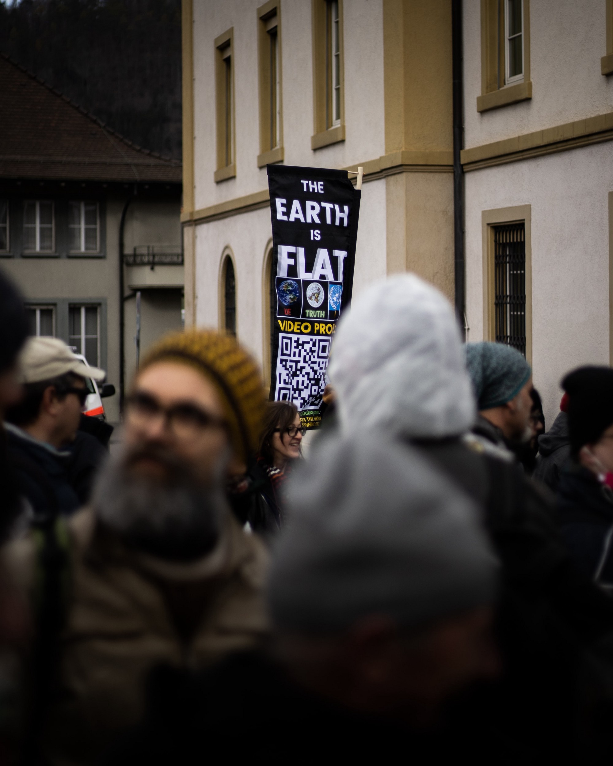 """People in the streets. One person is holding a black sign with white letters that say """"The Earth Is Flat."""" There are 3 pictures of the earth below that with the words """"Video Project"""" and a QR Code on the bottom."""
