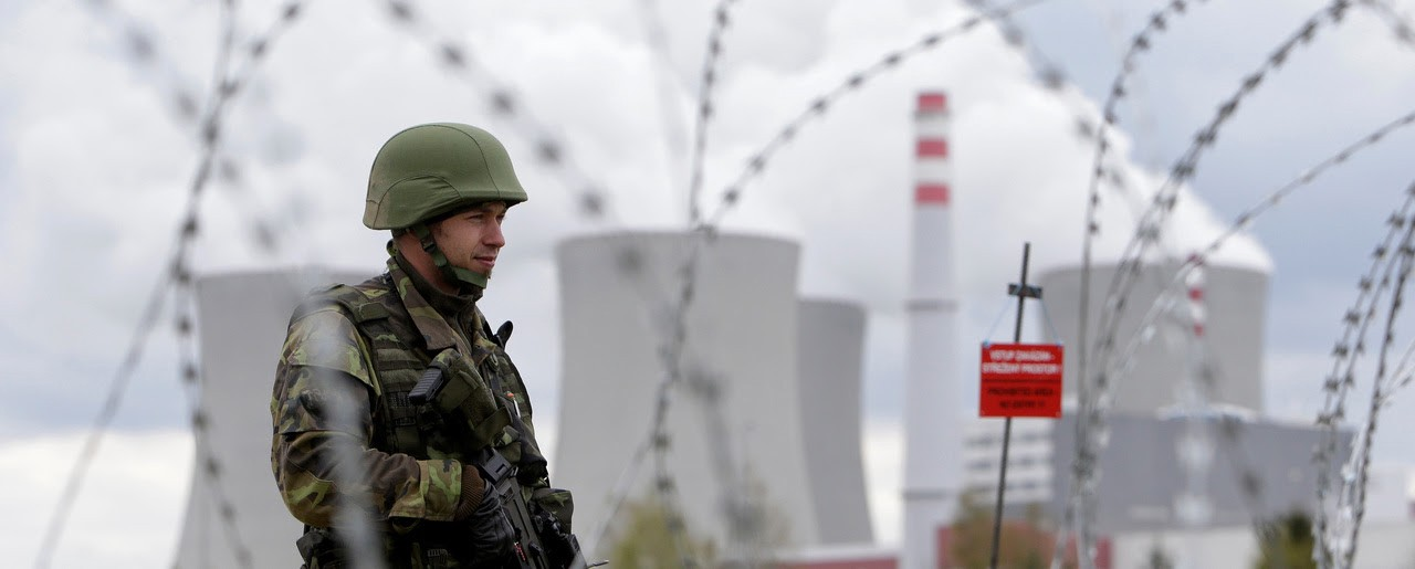 A military guard, framed by razor wire, stands on watch outside a power station, with cooling towers in the background