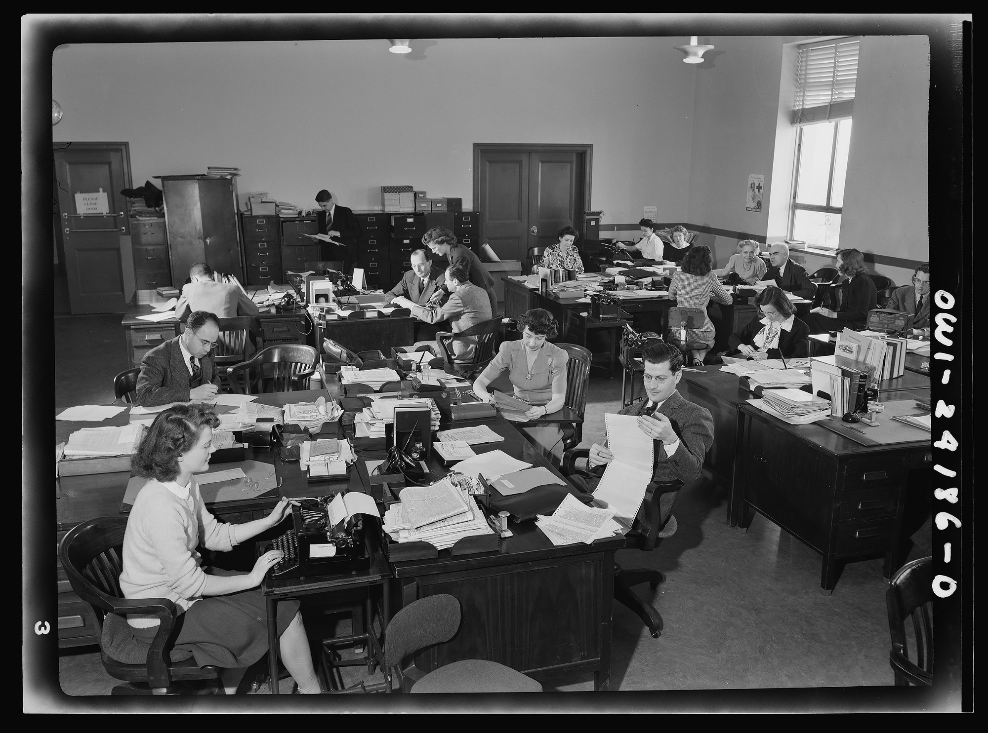 A group of professional women and men researching in a large government office using typewriters.
