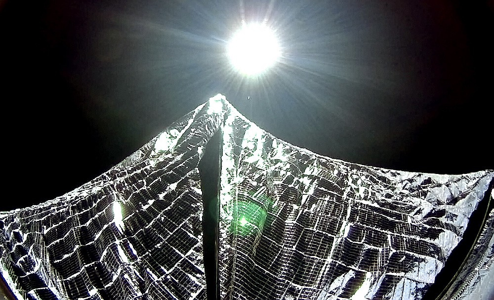 The Sun shines down on a solar sail in space.
