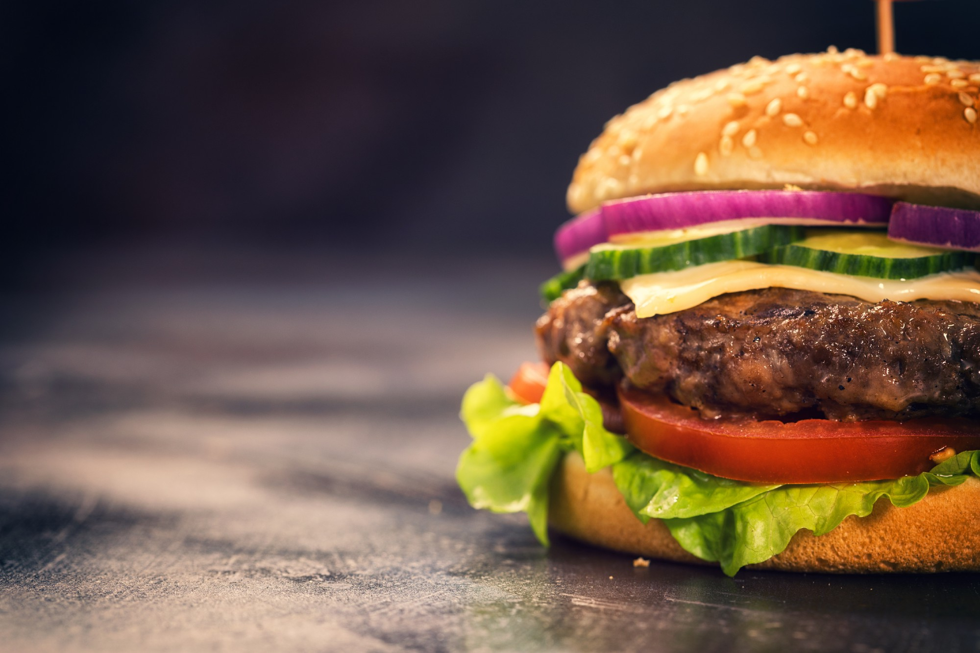 Close-up of a cheeseburger in a sesame seed bun with lettuce and sliced onions, tomatoes, and cucumbers on a black background