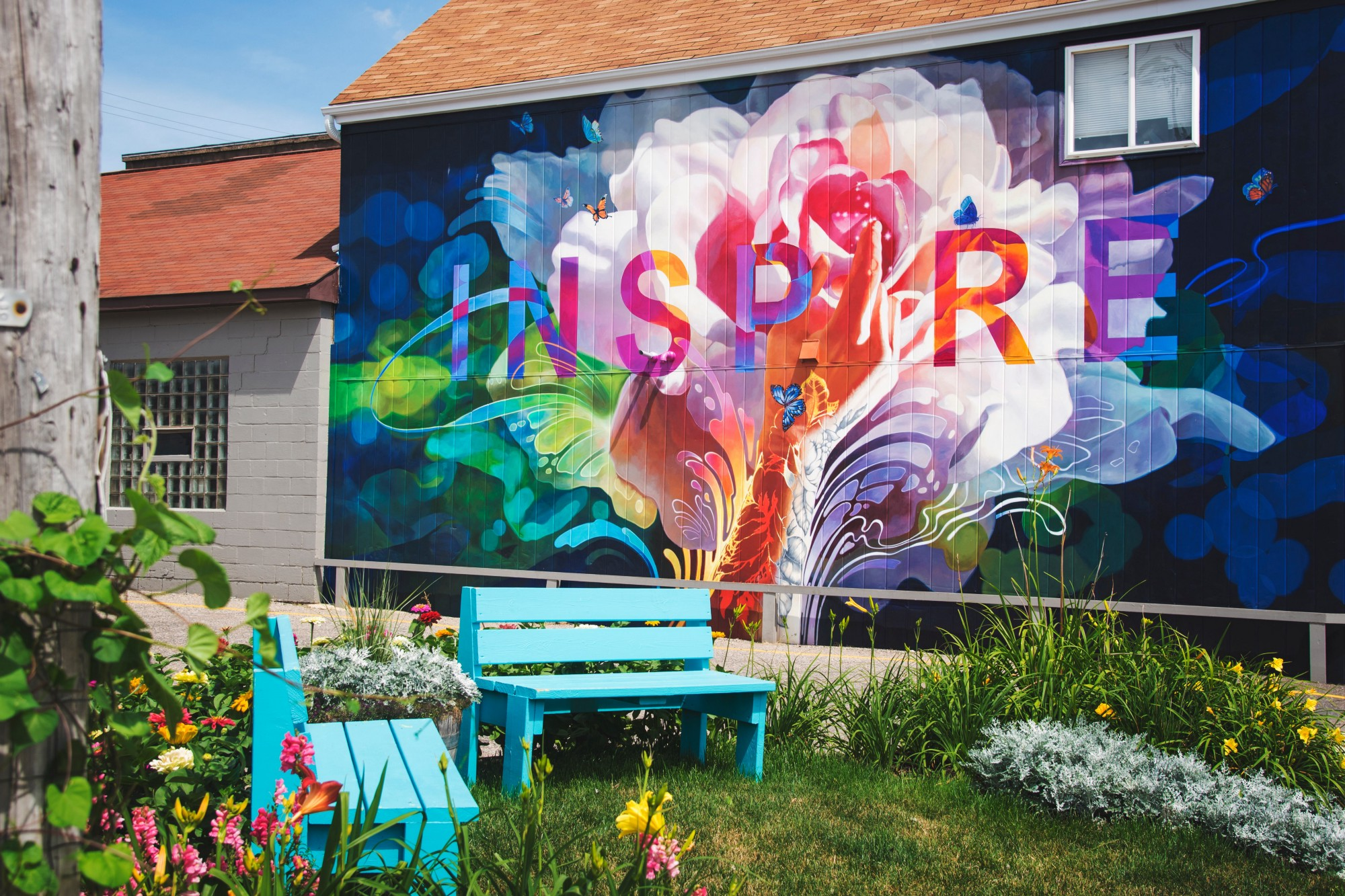 blue wooden benches near wall with graffiti, the word inspire on the wall