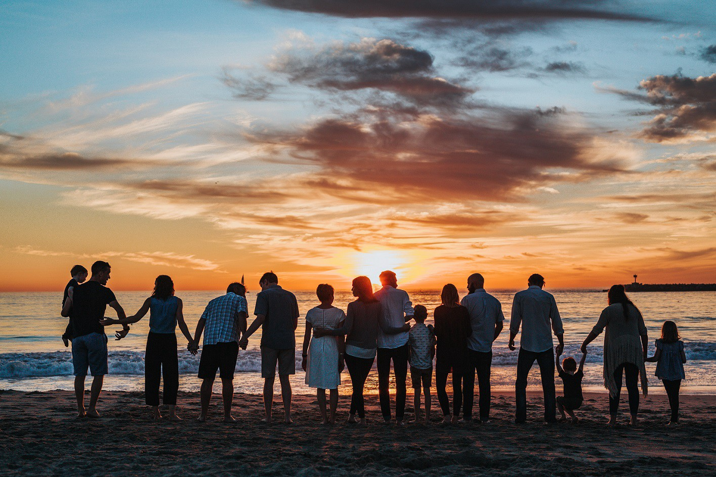 Multiple families enjoying time on a beach at sunset