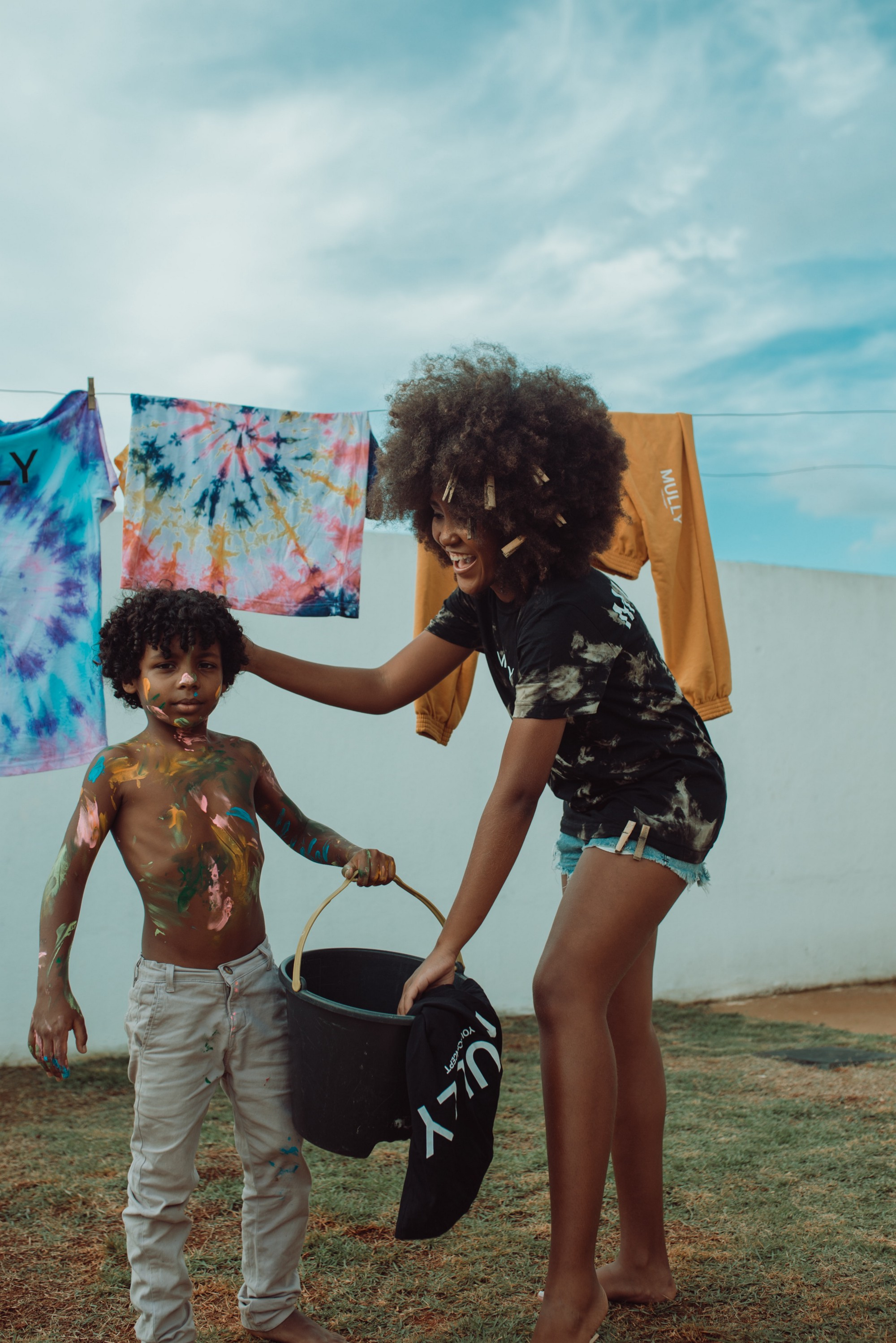Young shirtless boy and older girl hanging up closes on an outside close line.