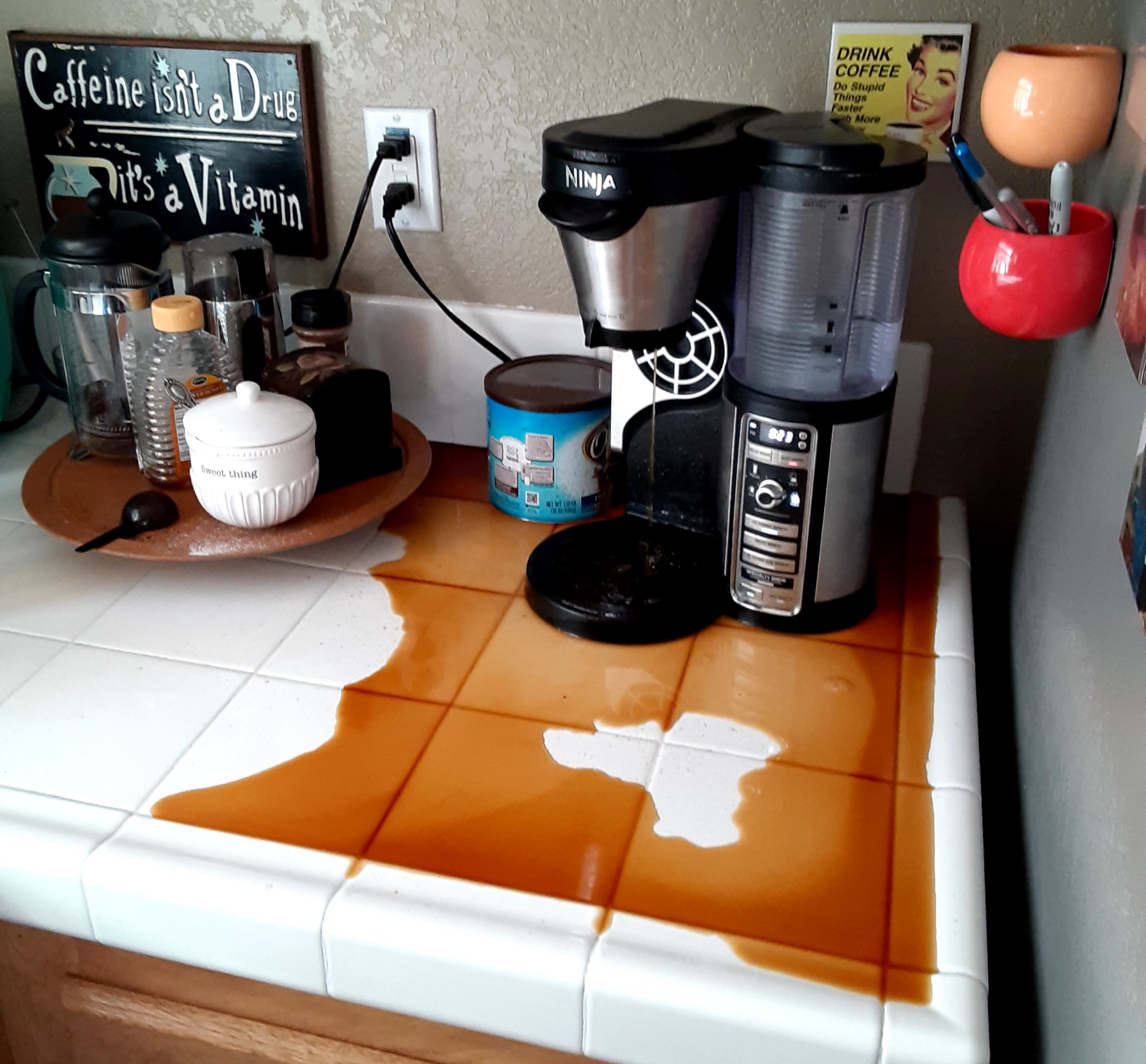 My real-life coffeemaker  without a carafe, coffee spilled widely over the countertop.