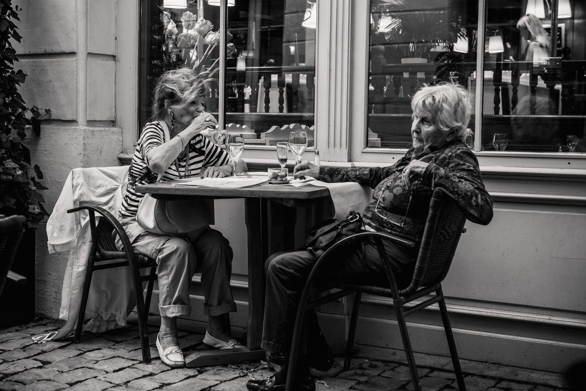 2 elderly ladies sat at a table enjoying a drink together