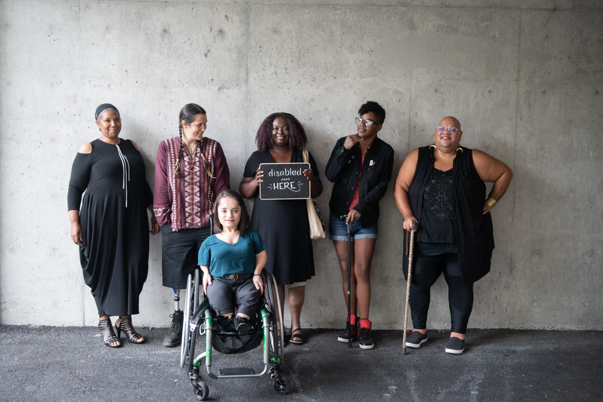 Six disabled people of colour smile and pose in front of a concrete wall.