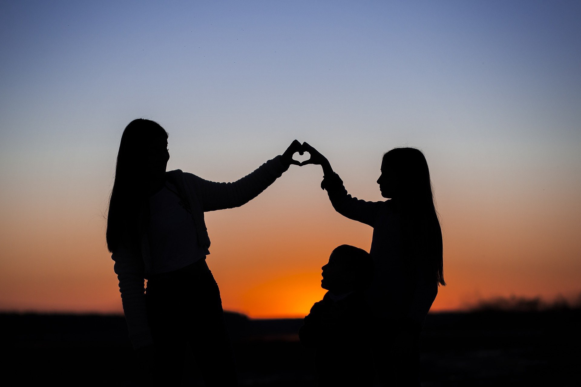 Three girls hanging out together with two of them forming the shape of a heart with their hands in the sunset
