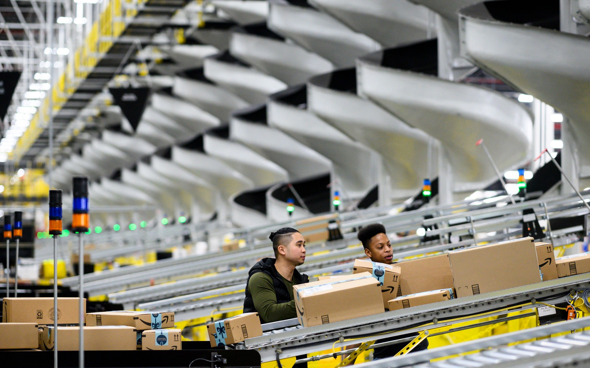 Men work at a distribution station in the 855,000-square-foot Amazon fulfillment center.