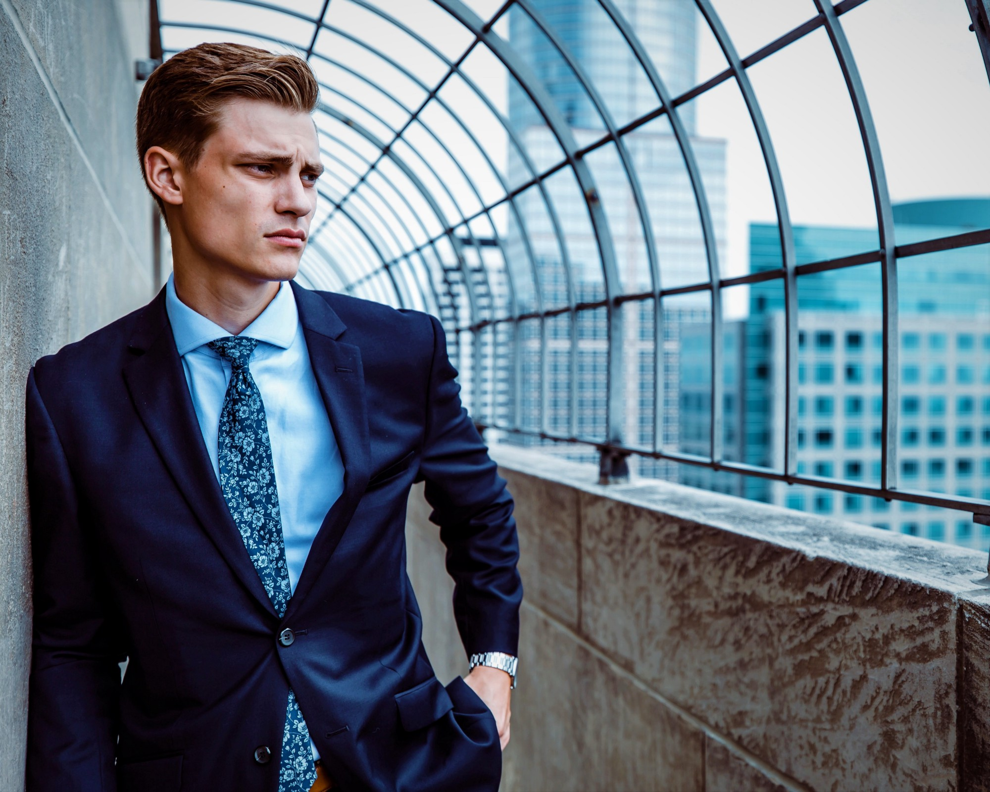 man in blue business suit and tie leaning against wall looking out over city skyline