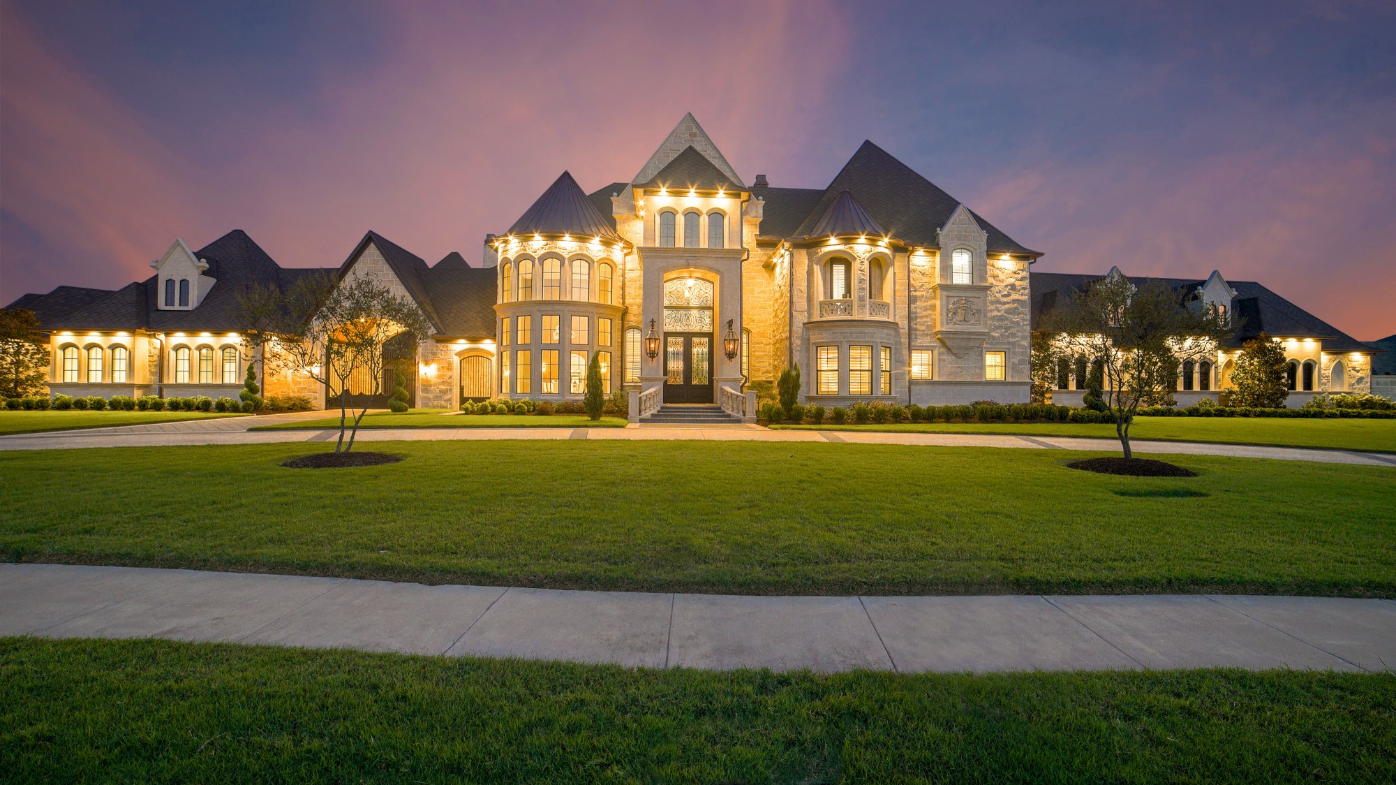 An obscenely large McMansion, faced with what appears to be rough fake stone, illuminated with all lights inside blazing yellow in the purple dusk. A wide swath of lawn extends from the circular drive to a sidewalk close to the camera.