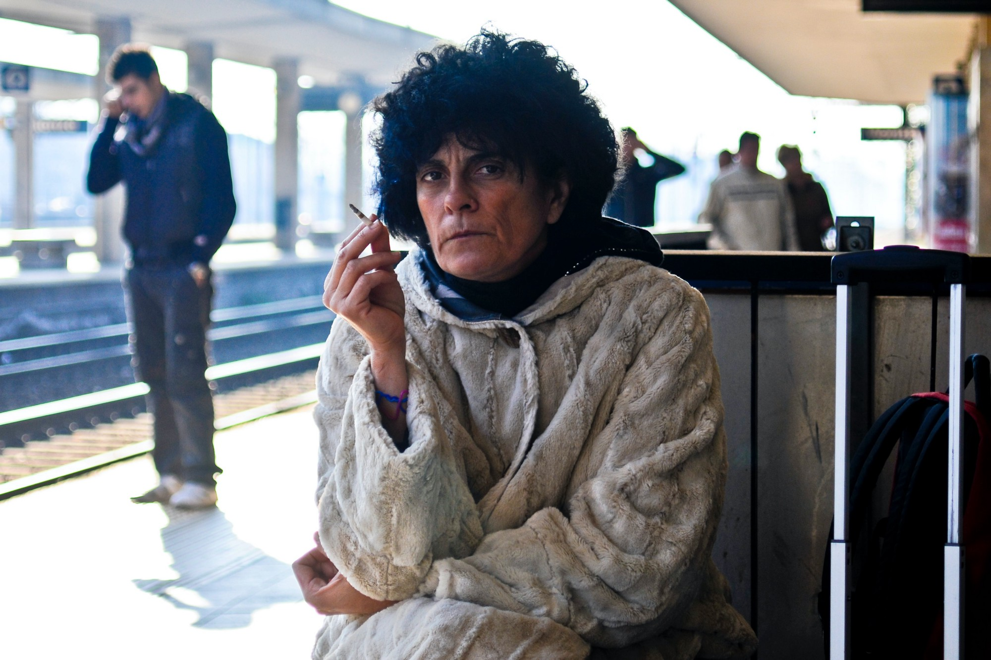 Curly haired woman in a sweater sitting at a train station smoking a cigarette and staring into the camera