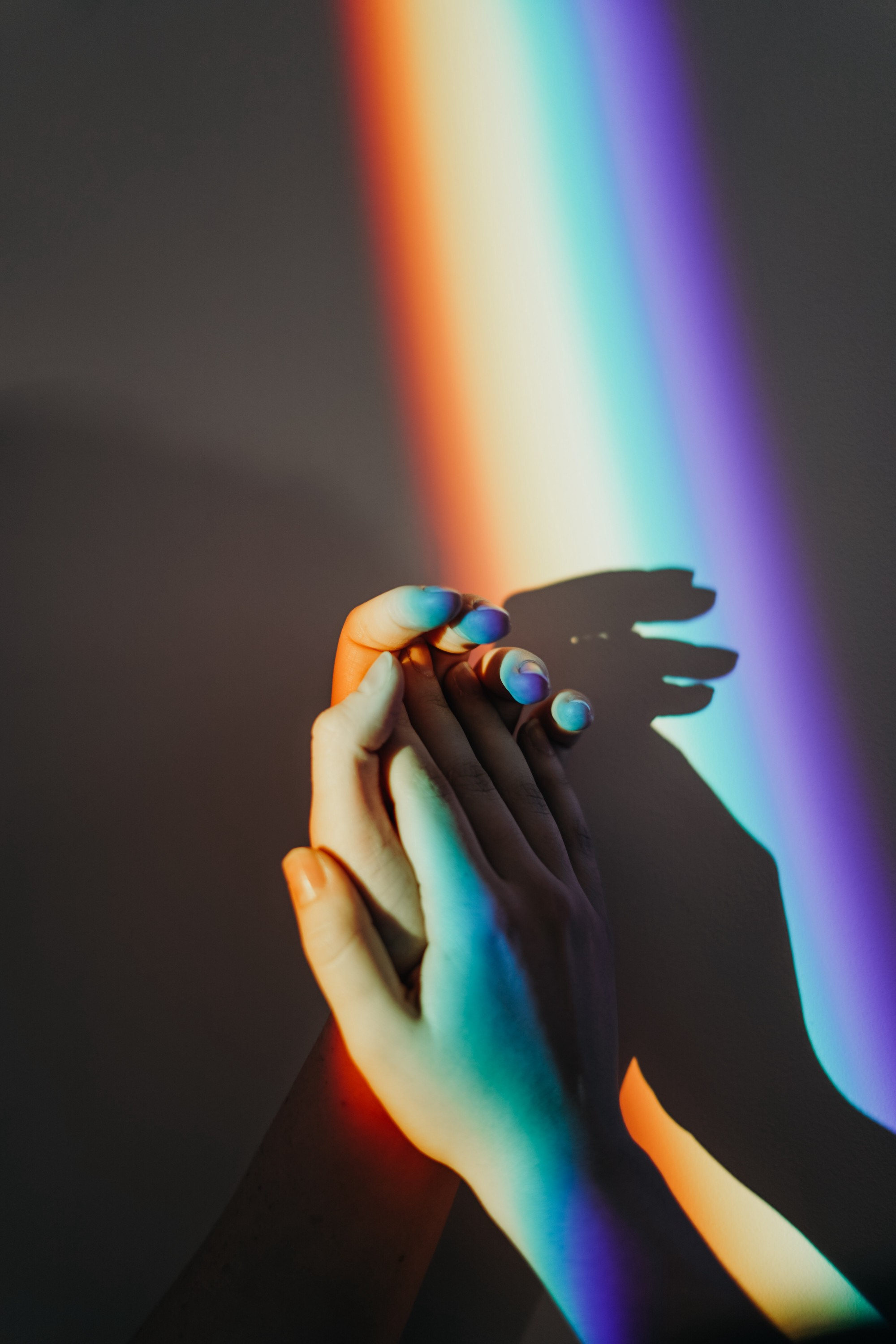 An image of two hands holding each other, with a rainbow light falling across them.