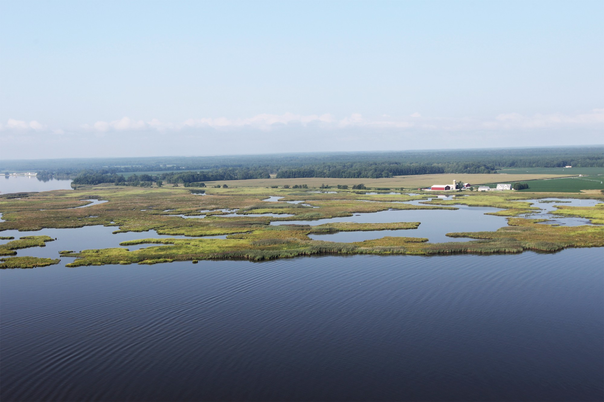 Aerial photo of river with marsh and farm in background