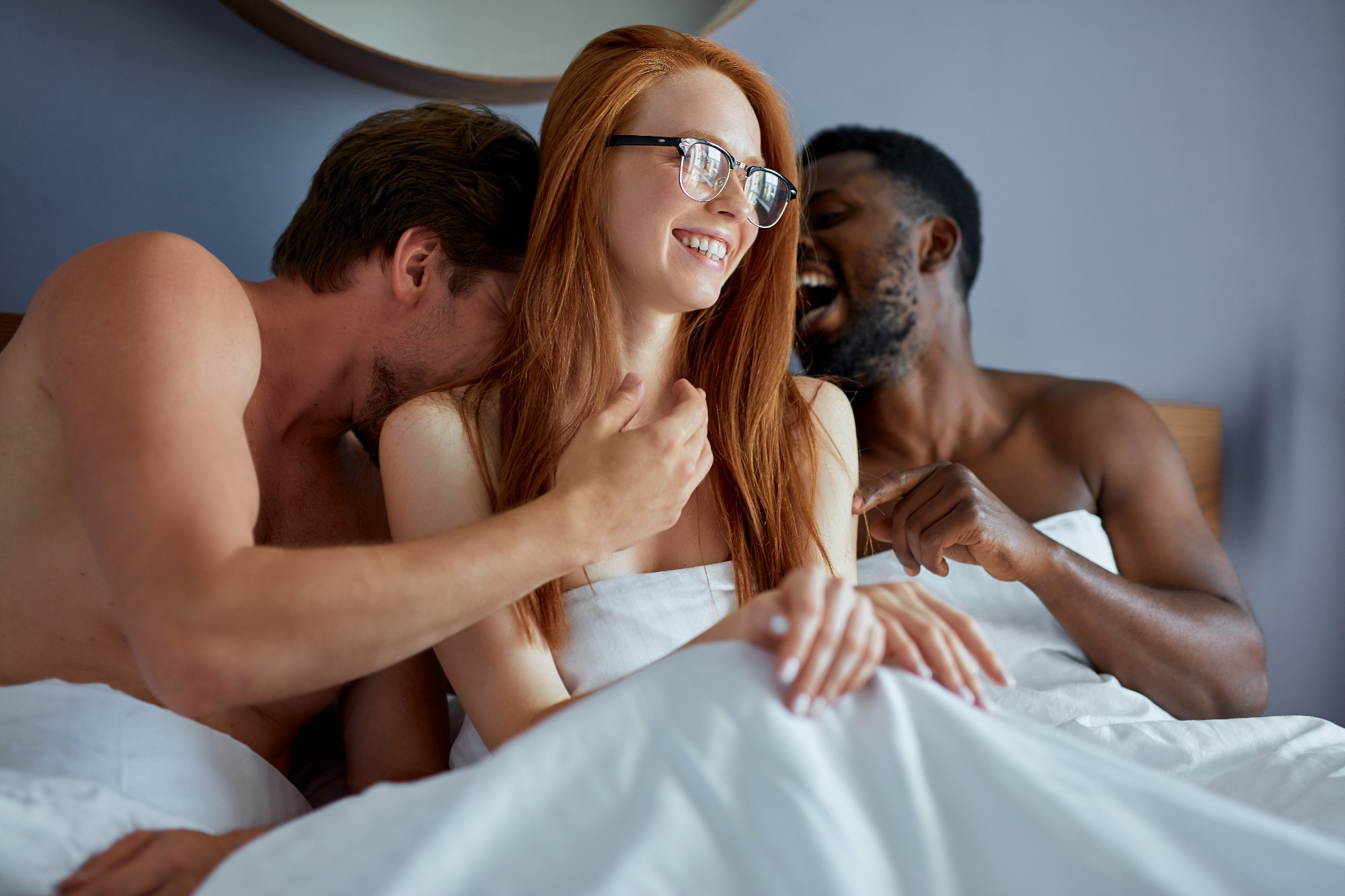 Two men and a woman are naked in bed under white sheets. One man is white, the other black. The woman is white with red hair and glasses. They are clearly intimate, but laughing as if having a relaxed time.