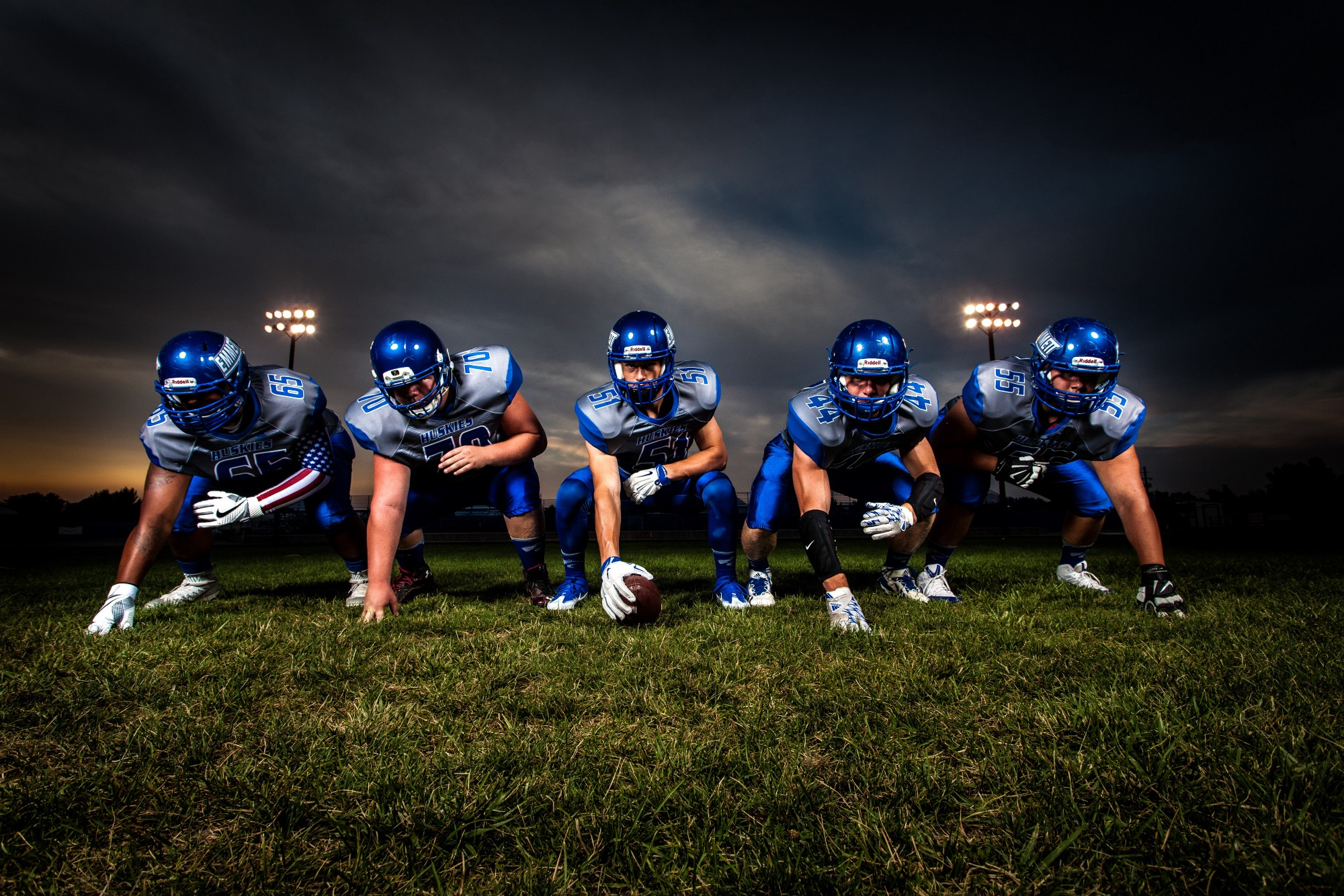 Football Players in Blue Jersey Lined Under Grey White Cloudy Sky during Sunset