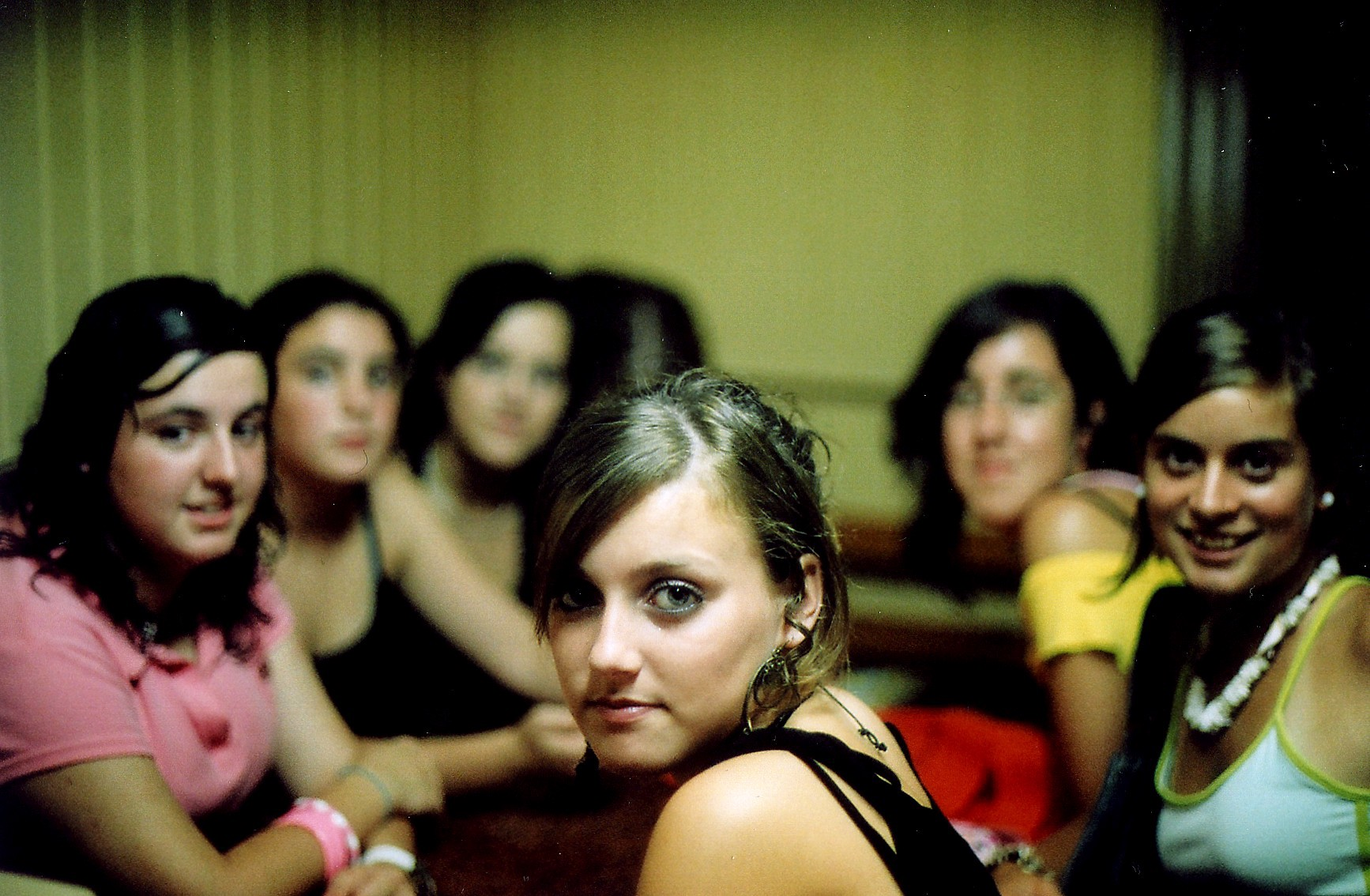 Bunch of young teen girls sitting around a table, looking judgmental