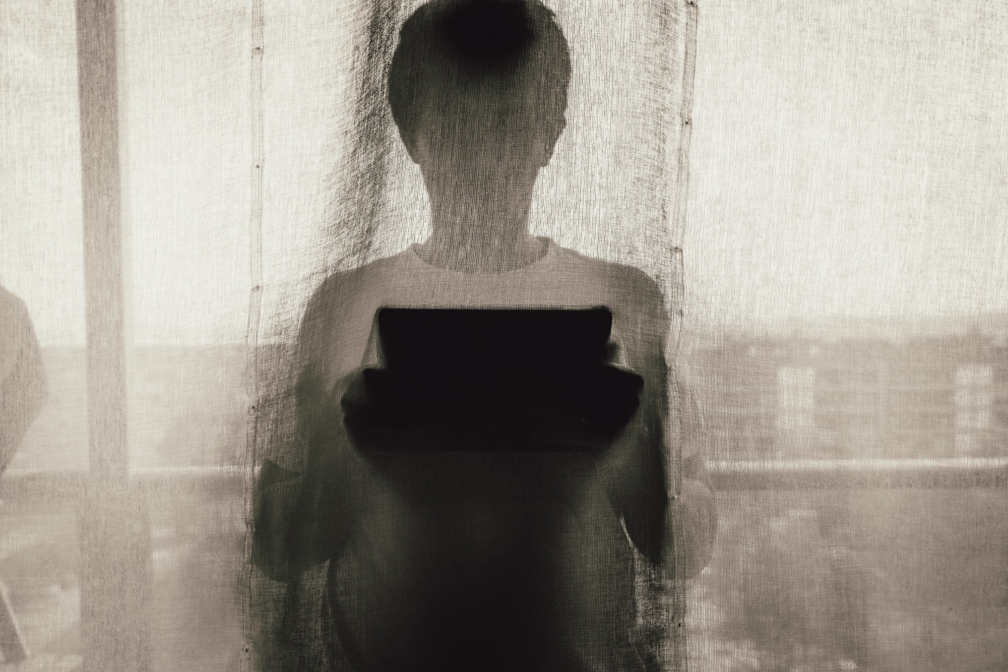 shrouded picture of boy with a tablet