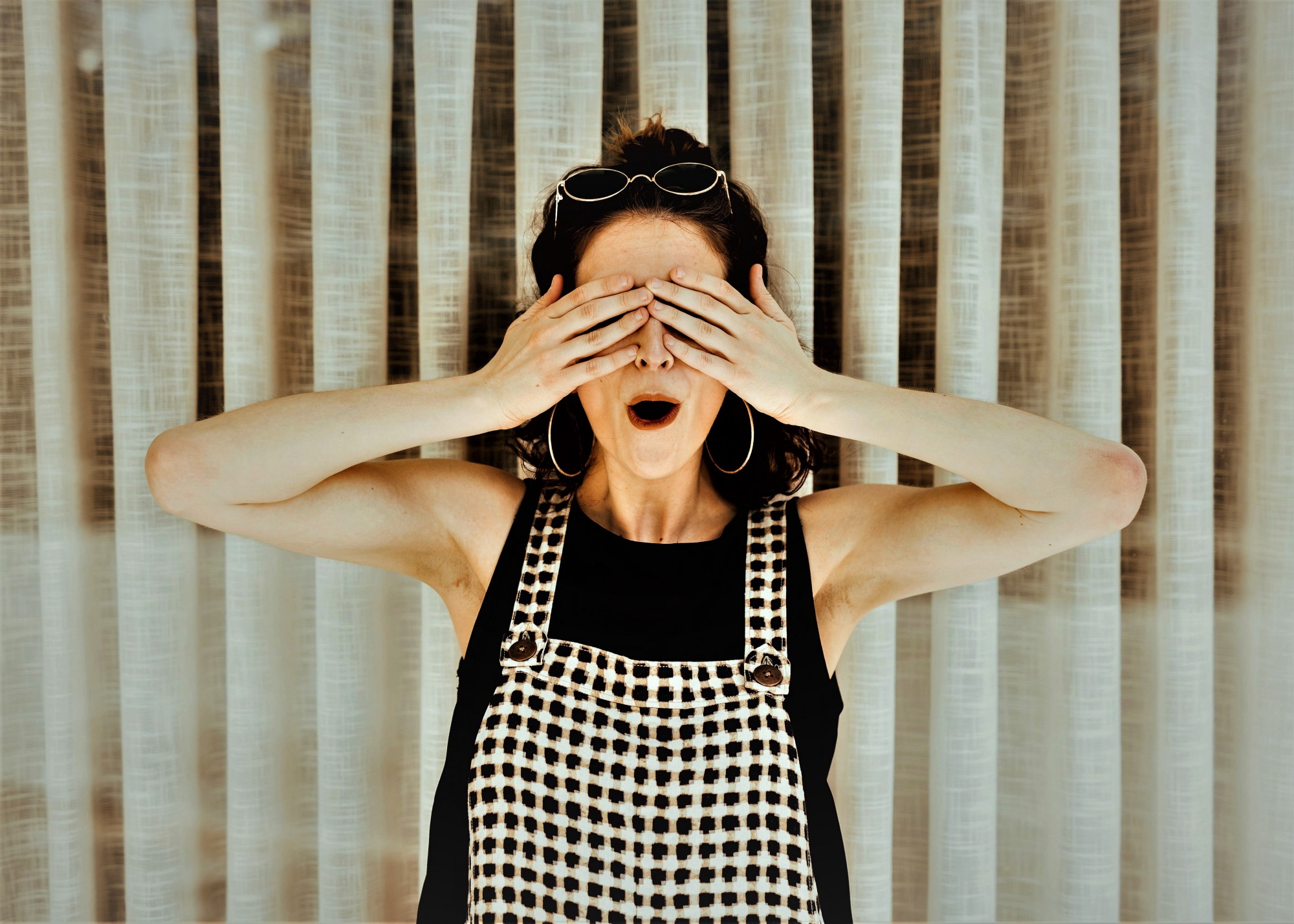 girl with dark hair wearing black and white checked top standing in front of light color curtain holding her hands over her eyes