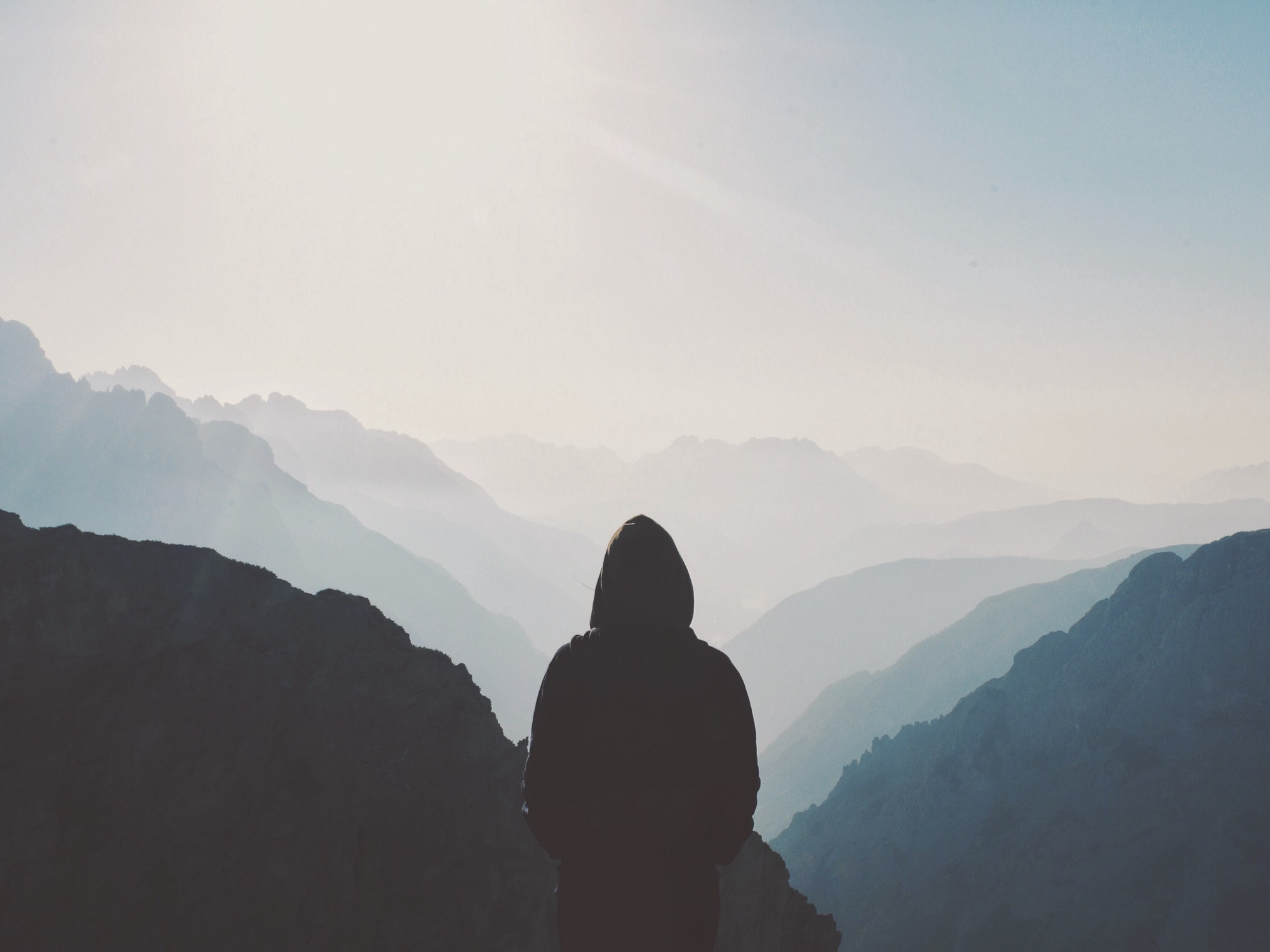 A hooded figure staring at a mountain valley