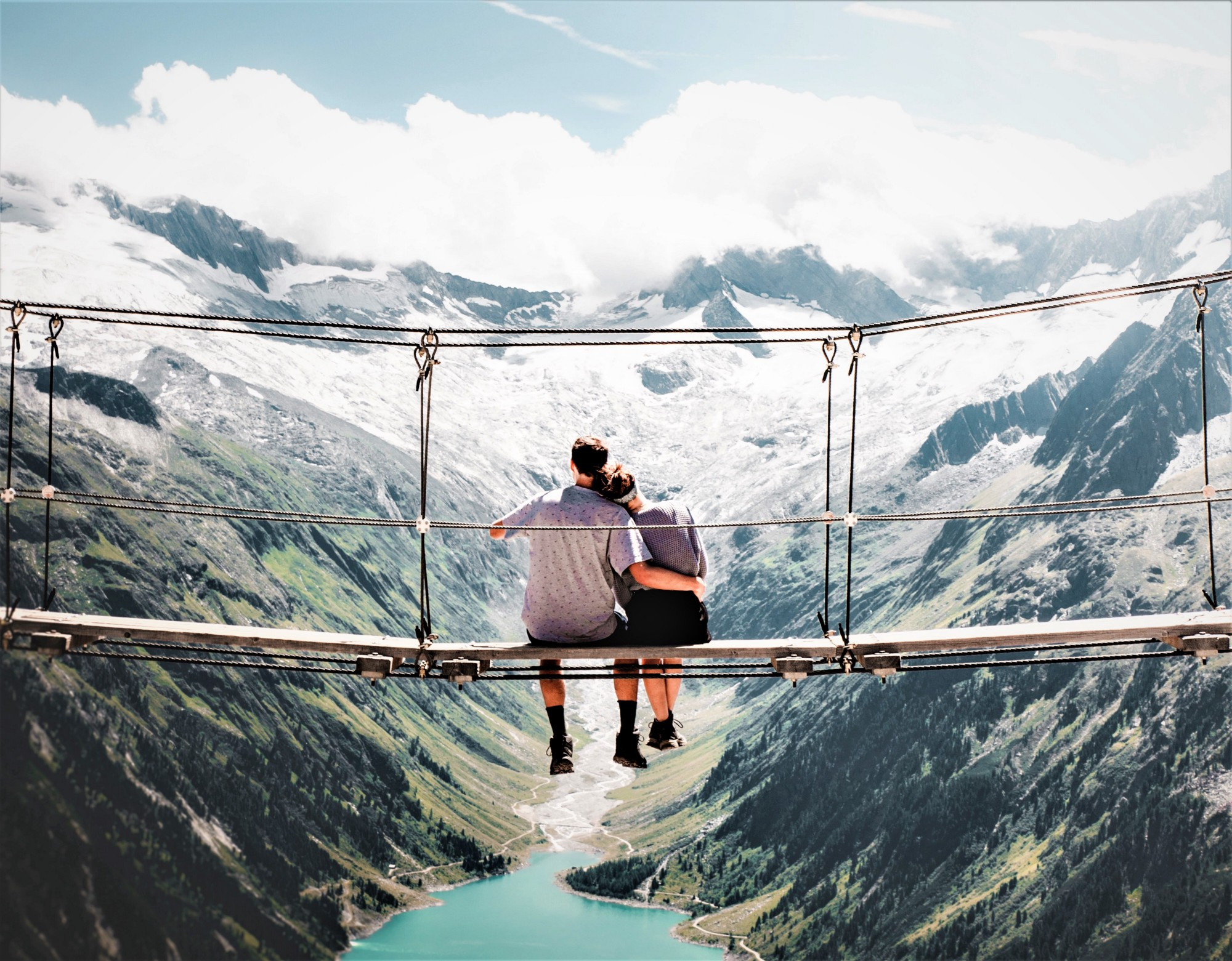 picture of couple sitting on walking bridge looking out over canyon and river
