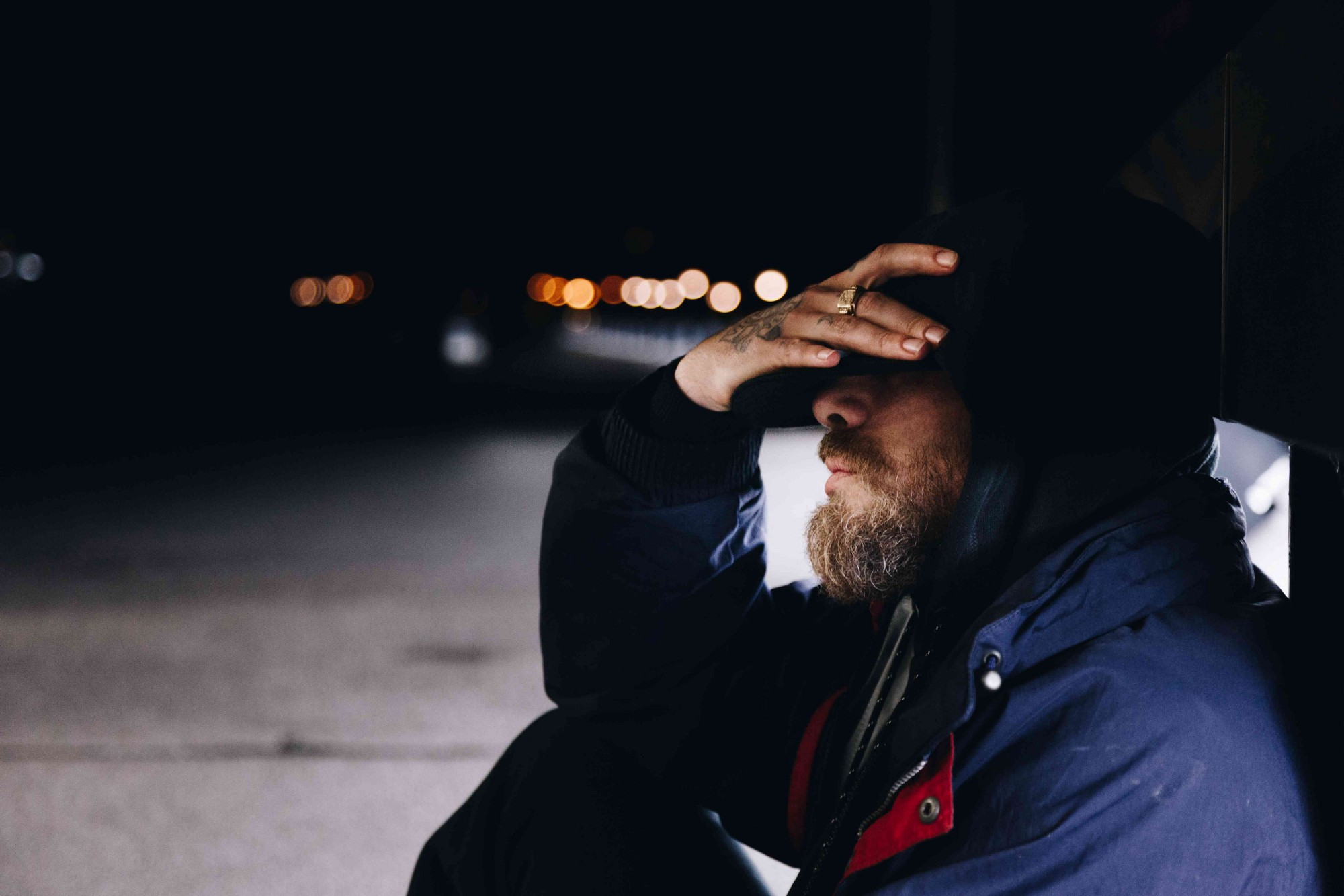 Man sitting on a sidewalk in the dark, with hand covering eyes.