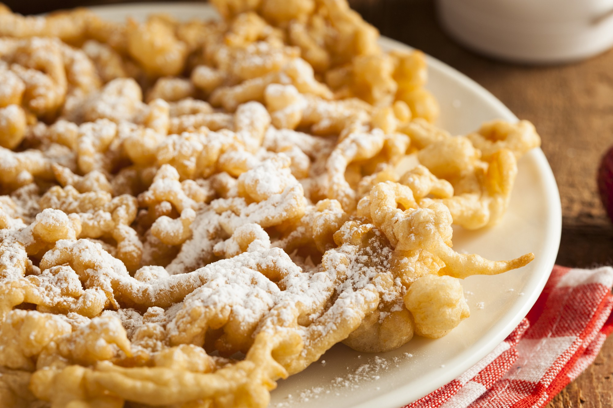 A plate of a powdered sugar-dusted funnel cake, on a red-and-white gingham cloth.