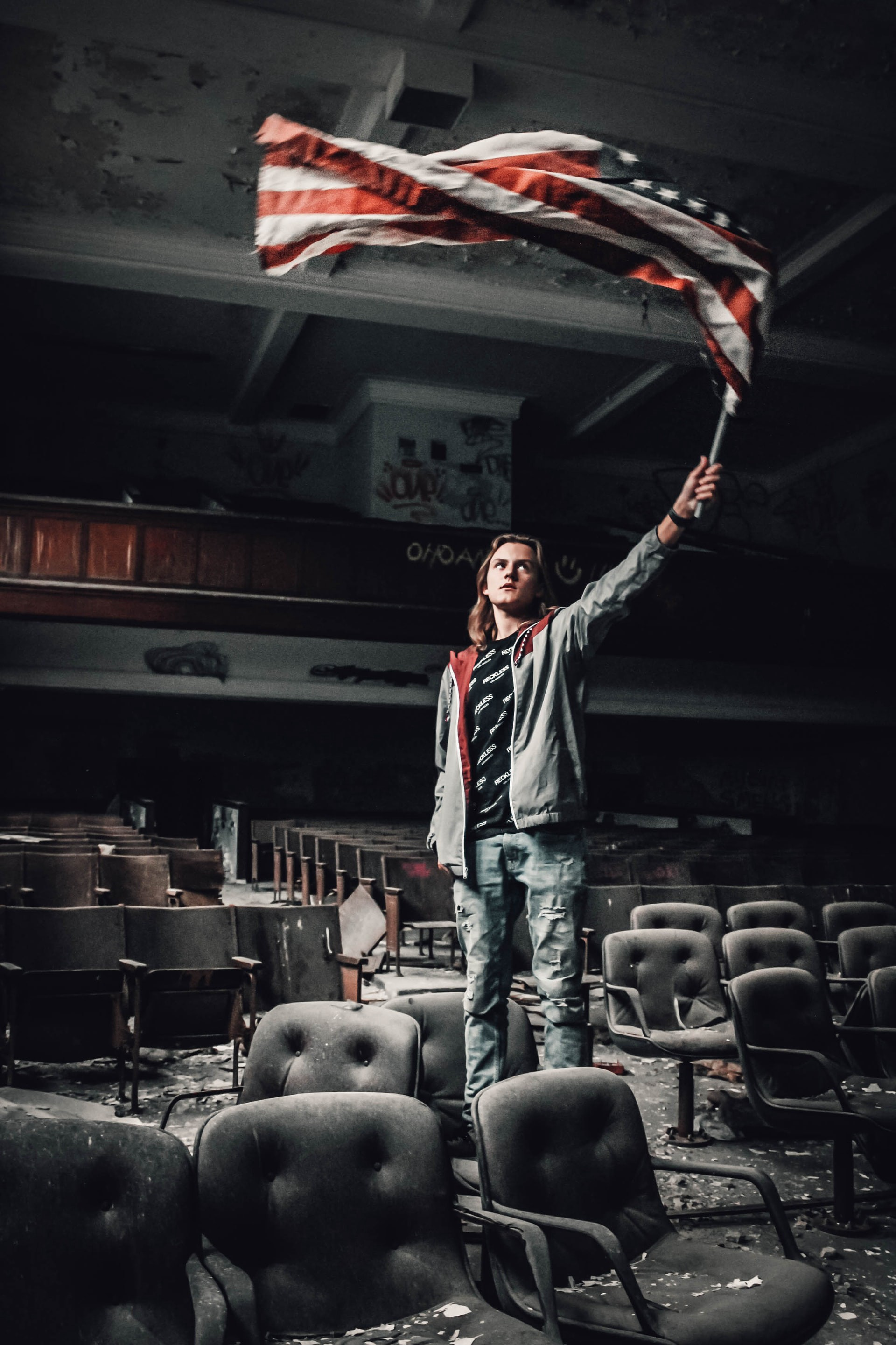 Young man waving an American flag in an old decaying empty theatre.
