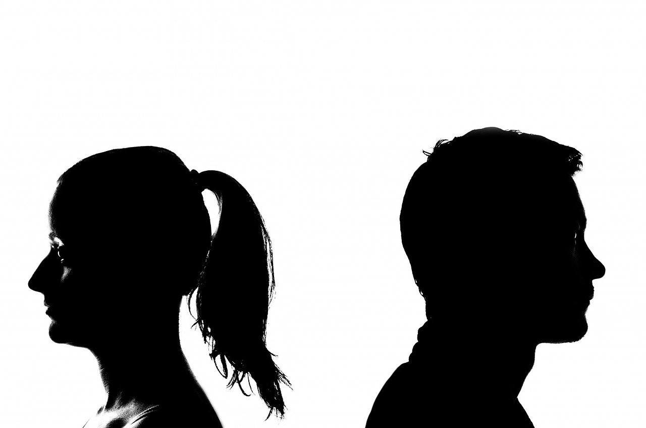 A black and white picture of people in profile facing opposite directions