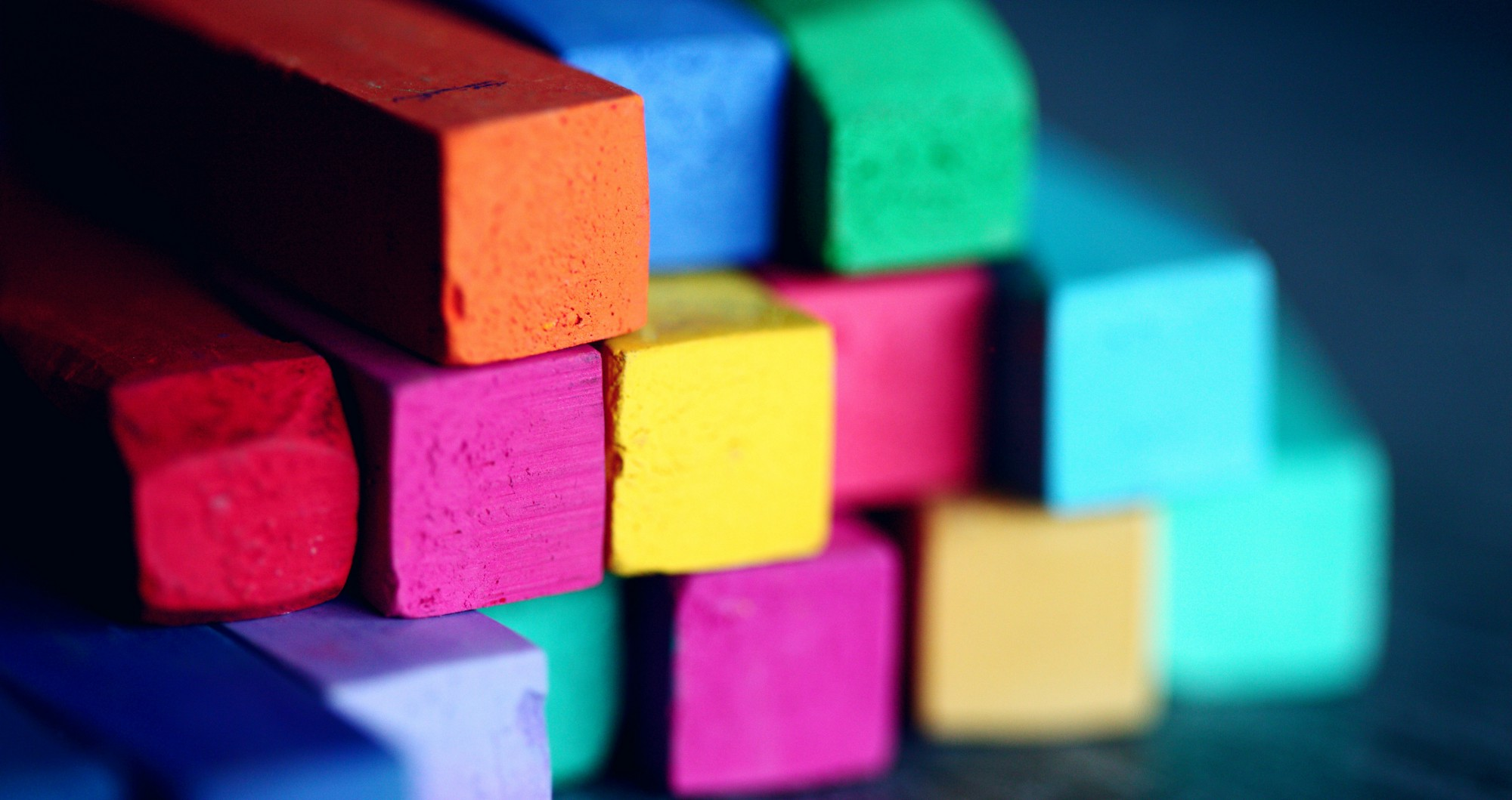 Brightly coloured building blocks stacked loosely on top of each other.