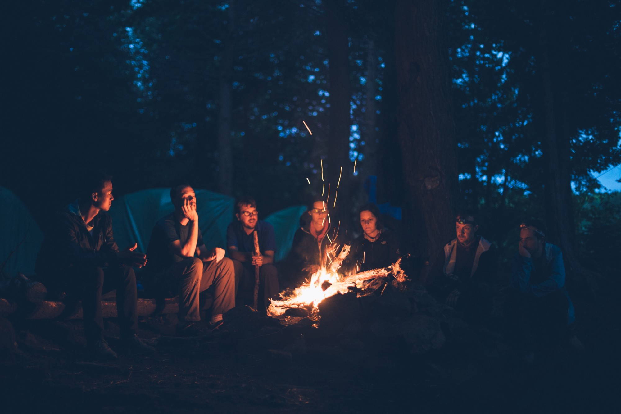 A group of people sitting at a campfire listening to stories