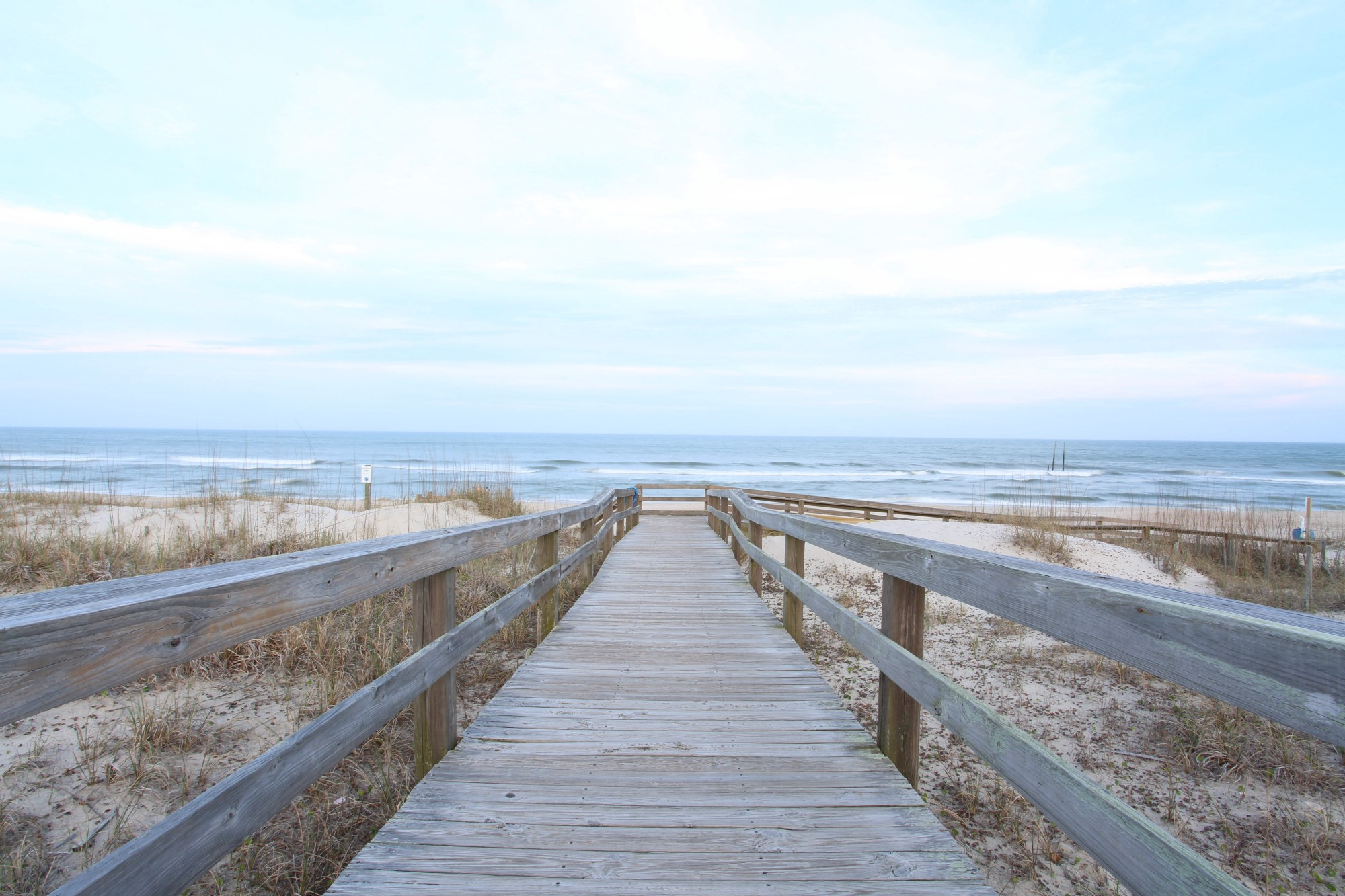 A boardwalk on the beach, leading from the sand, down to the ocean.