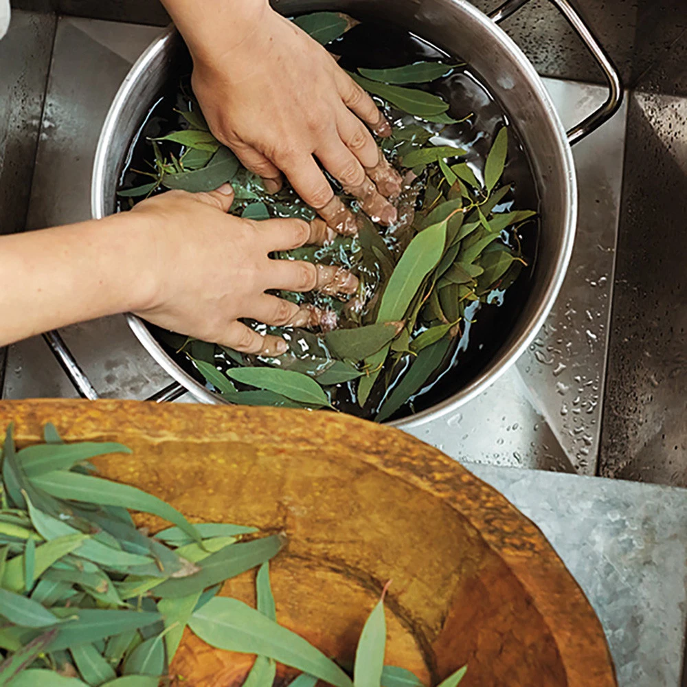 Hands wash leaves in a metal pot.