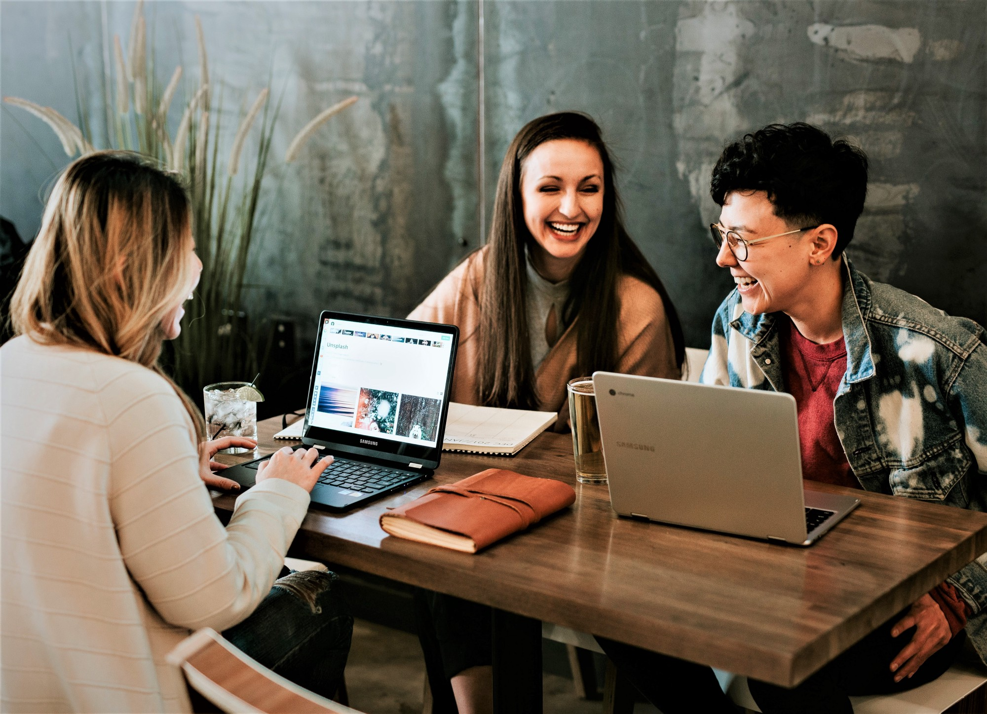 three young adults sitting around wooden table with computer laughing, smiling, and talking