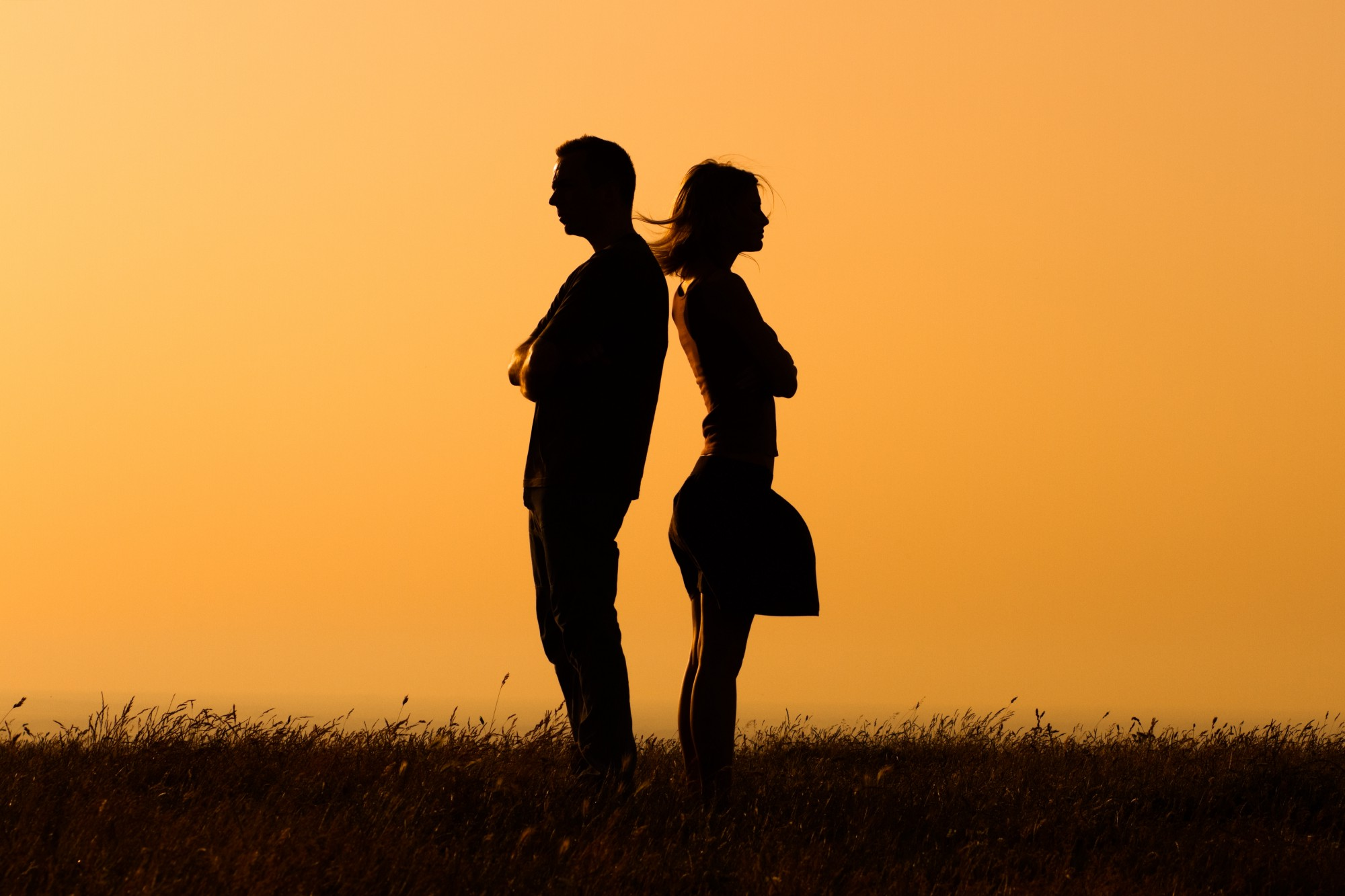 A man and a woman stand back to back, silhouetted against a dark orange, evening sky.