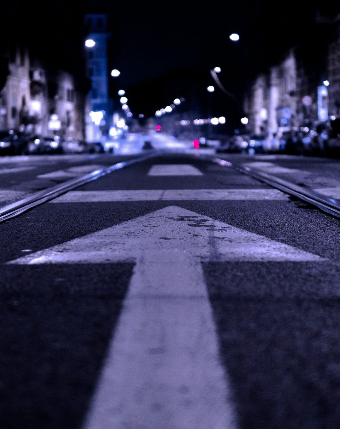 Streetscape at night featuring a city street with an arrow painted on it, pointing straight ahead