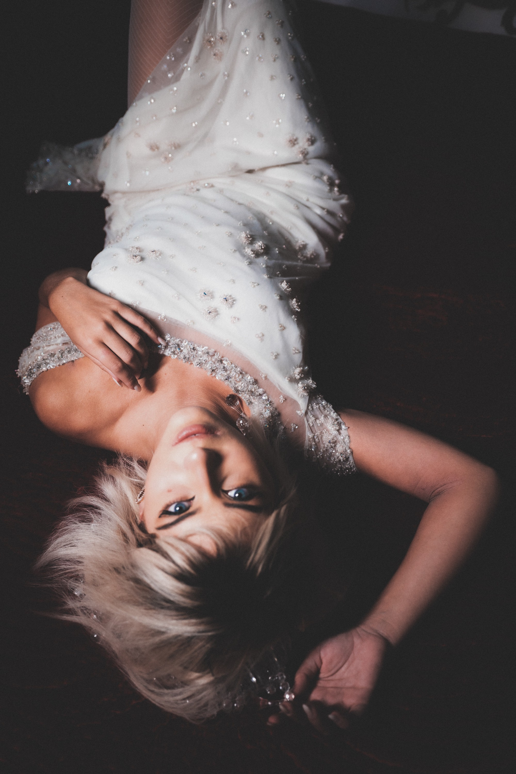 Sexy bride lying down her back in a bejeweled white gown