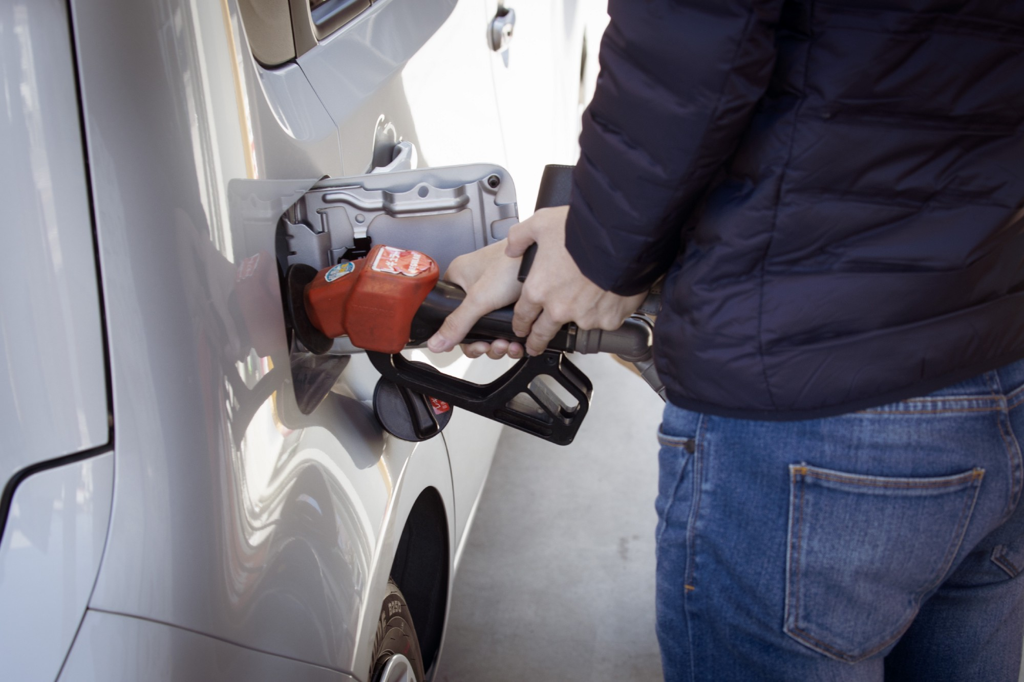 A man in a blue jack and blue jeans pumps gasoline into his white hatchback car.