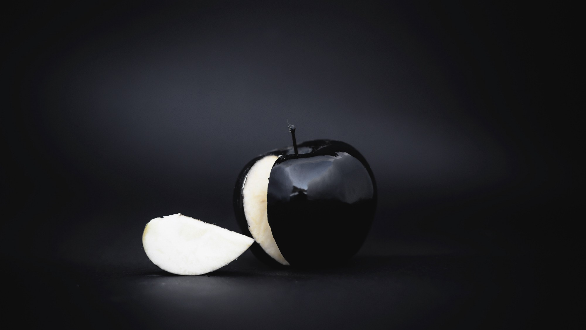 Black shadowed background with black apple and white slice cut out