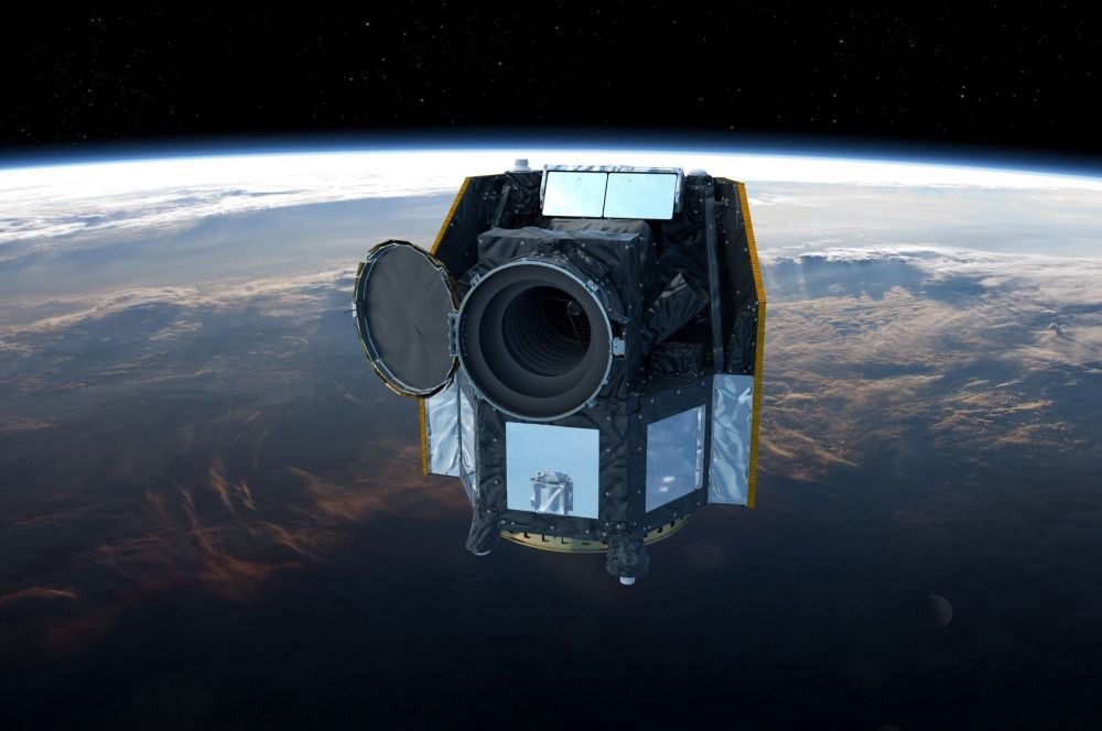 A dark, boxy-looking satelitte is pictured in orbit above Earth.