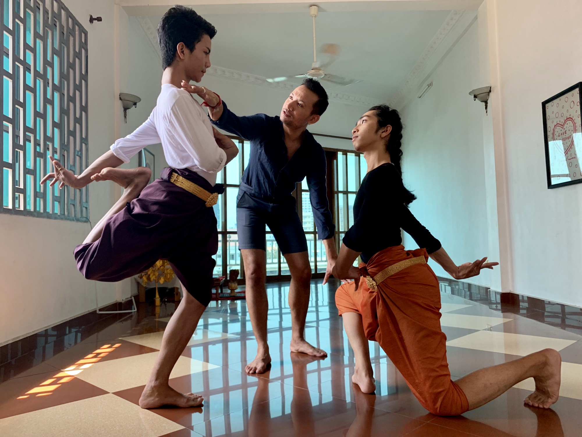 Man instructs two male dancers in Cambodian dance in a dance studio