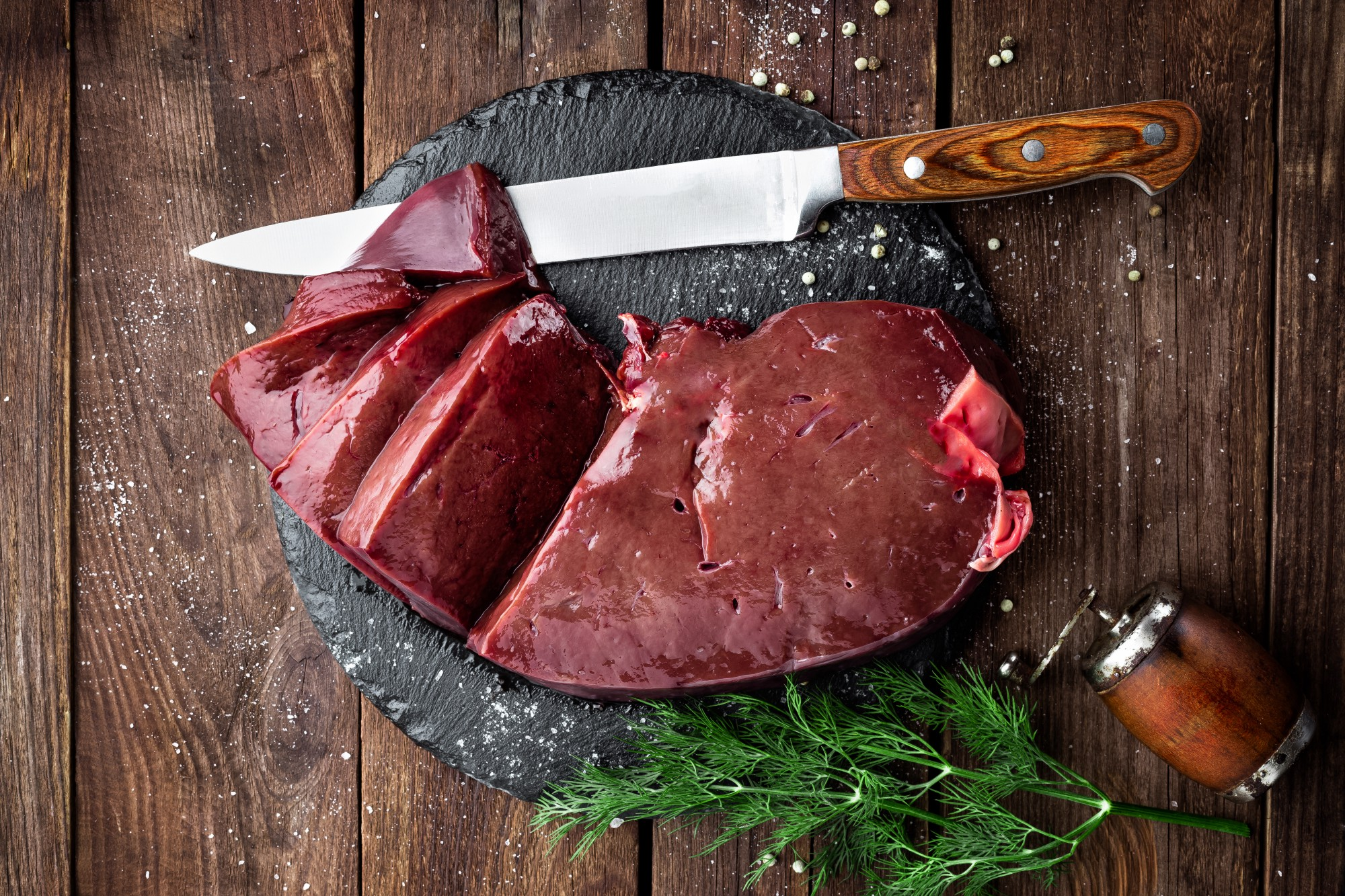 Beef liver being sliced on a black cutting board with wooden plank background.