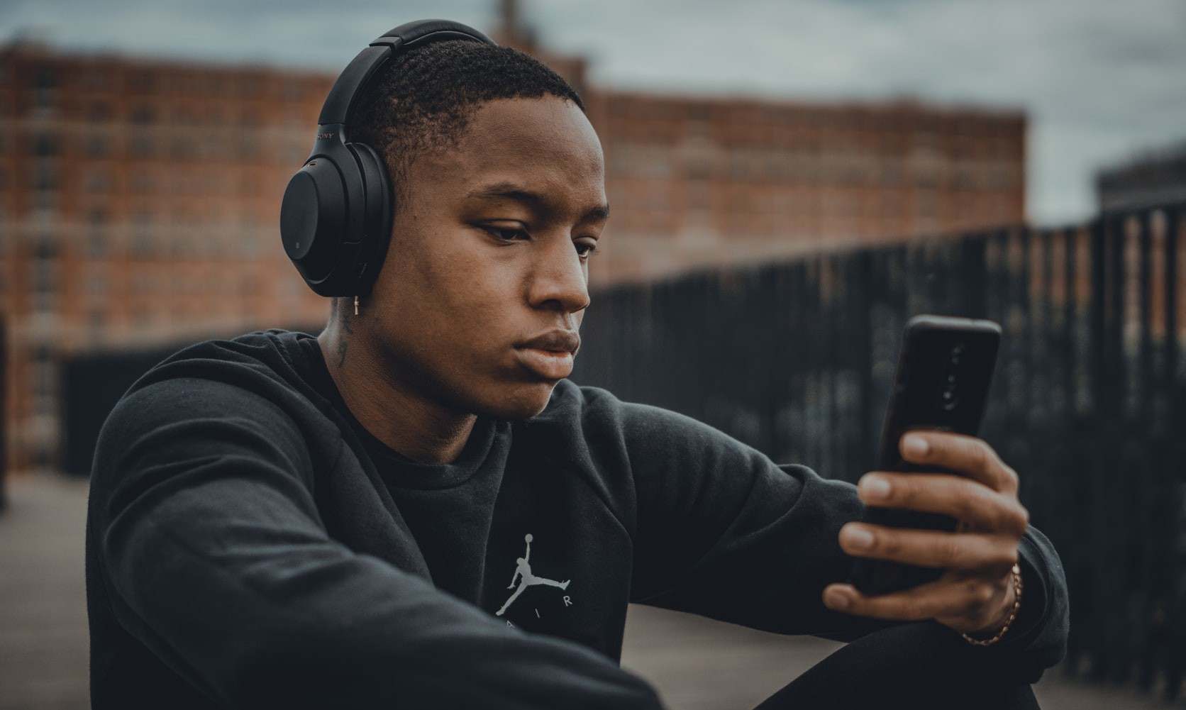 Man wearing headphones looks at a cellphone.